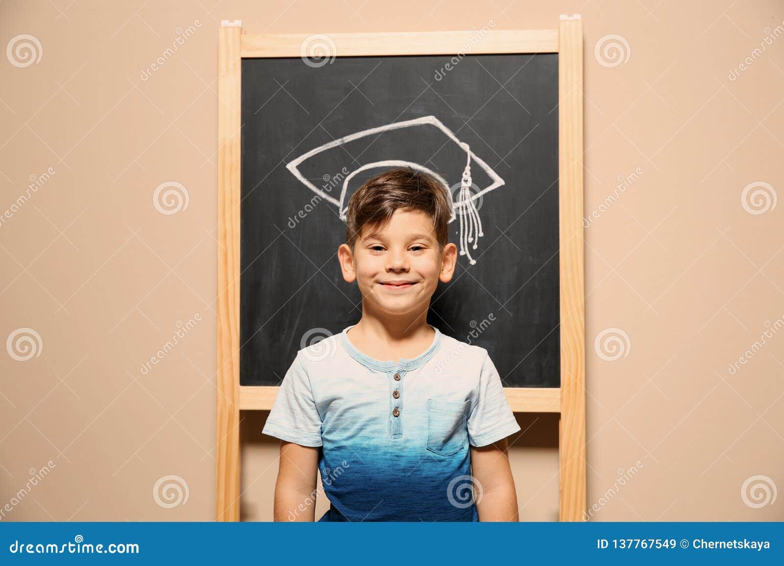 Leuk weinig kind die zich bij bord met krijt getrokken academisch GLB bevinden