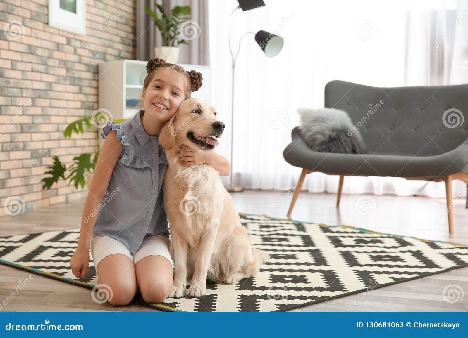Leuk weinig kind met haar huisdier op vloer