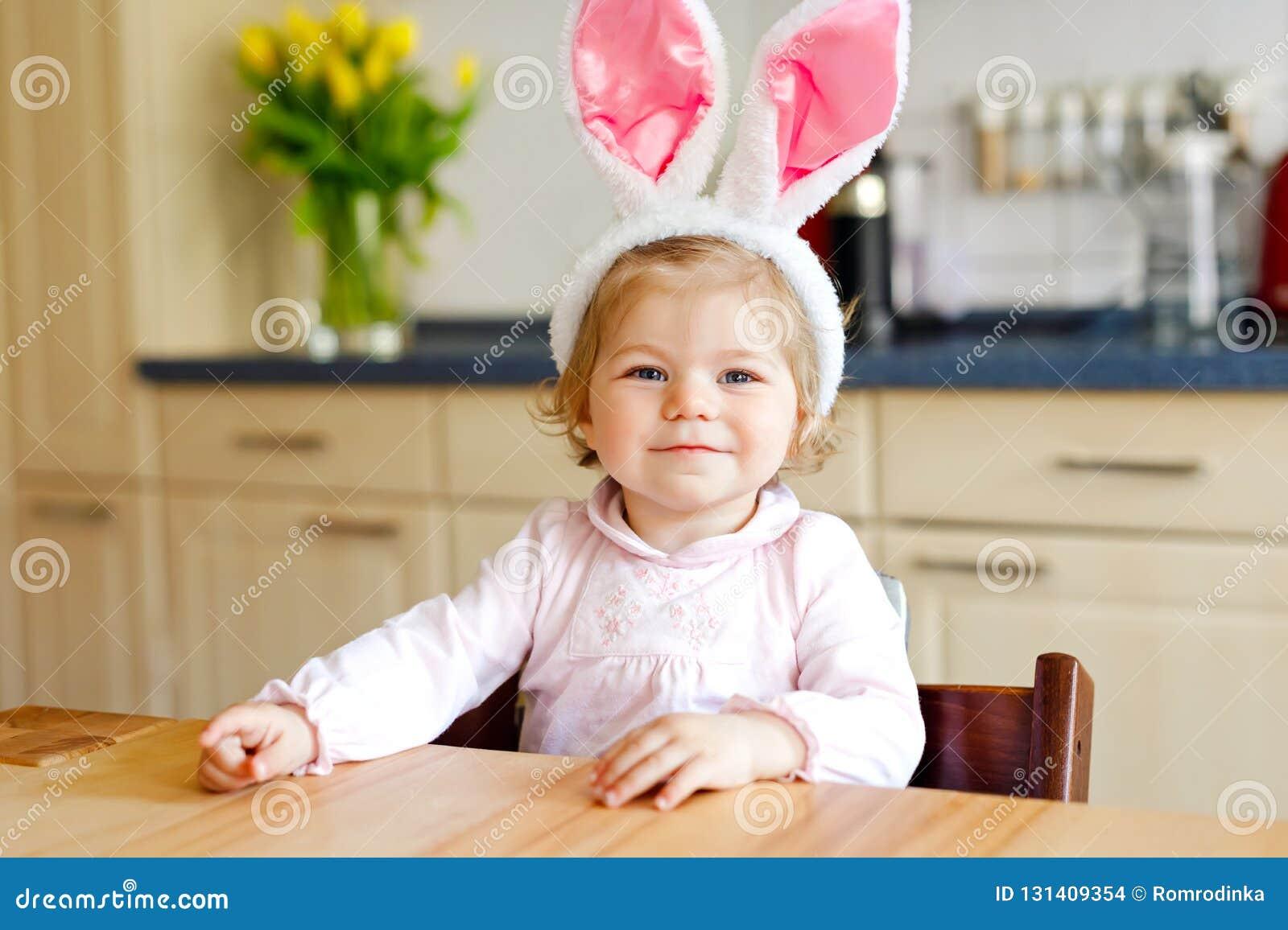 Leuk weinig peutermeisje die Paashaasoren dragen die met gekleurde pastelkleureieren spelen De gelukkige uitpakkende giften van h