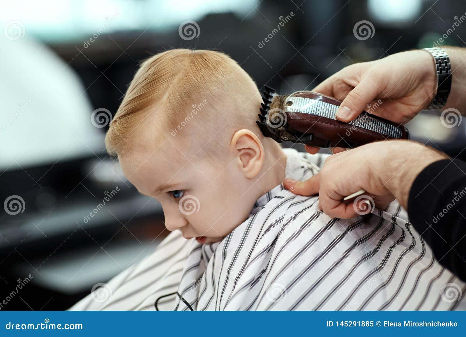 Leuke blonde babyjongen met blauwe ogen in een kapperswinkel die kapsel hebben door kapper Handen van stilist met hulpmiddelen
