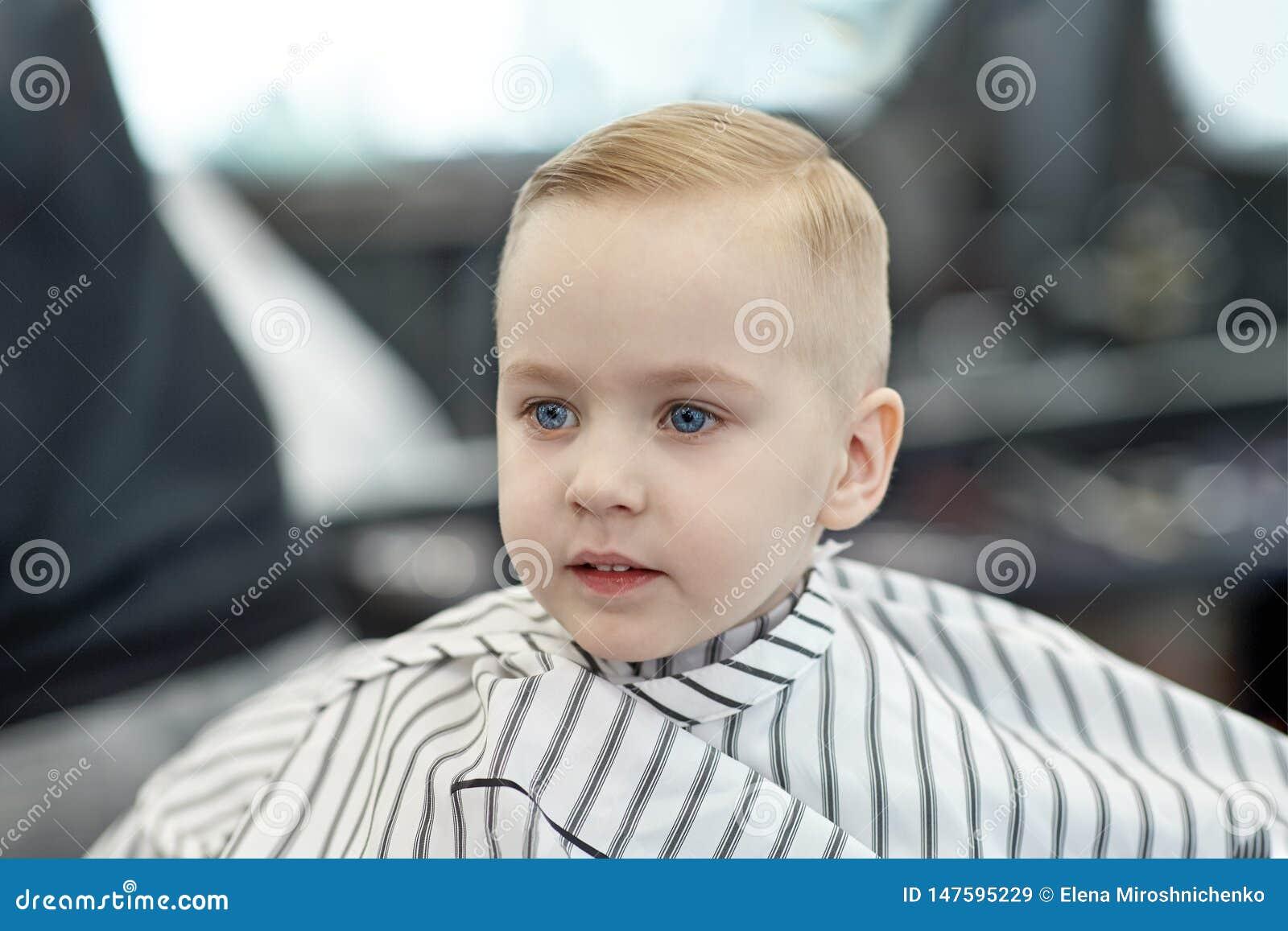 Leuke blonde glimlachende babyjongen met blauwe ogen in een kapperswinkel na kapsel door kapper De kinderen vormen in salon