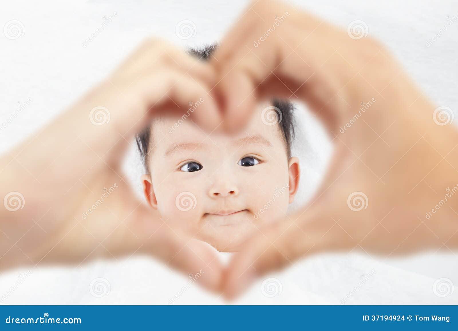 Leuke en glimlachende zuigeling met de handen van de oudersliefde