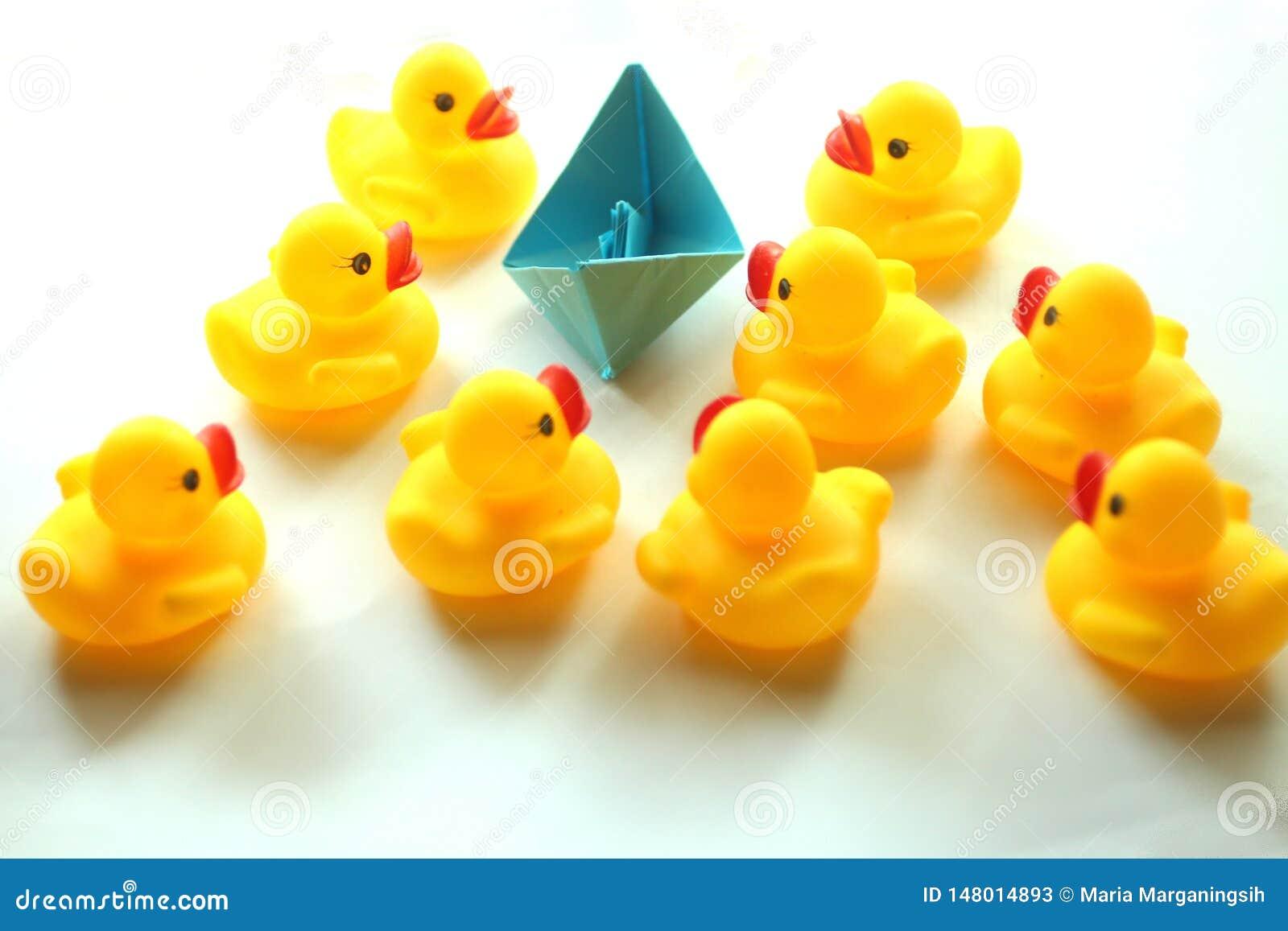Leuke gele rubbereenden en één document origamiboot in blauwe kleur