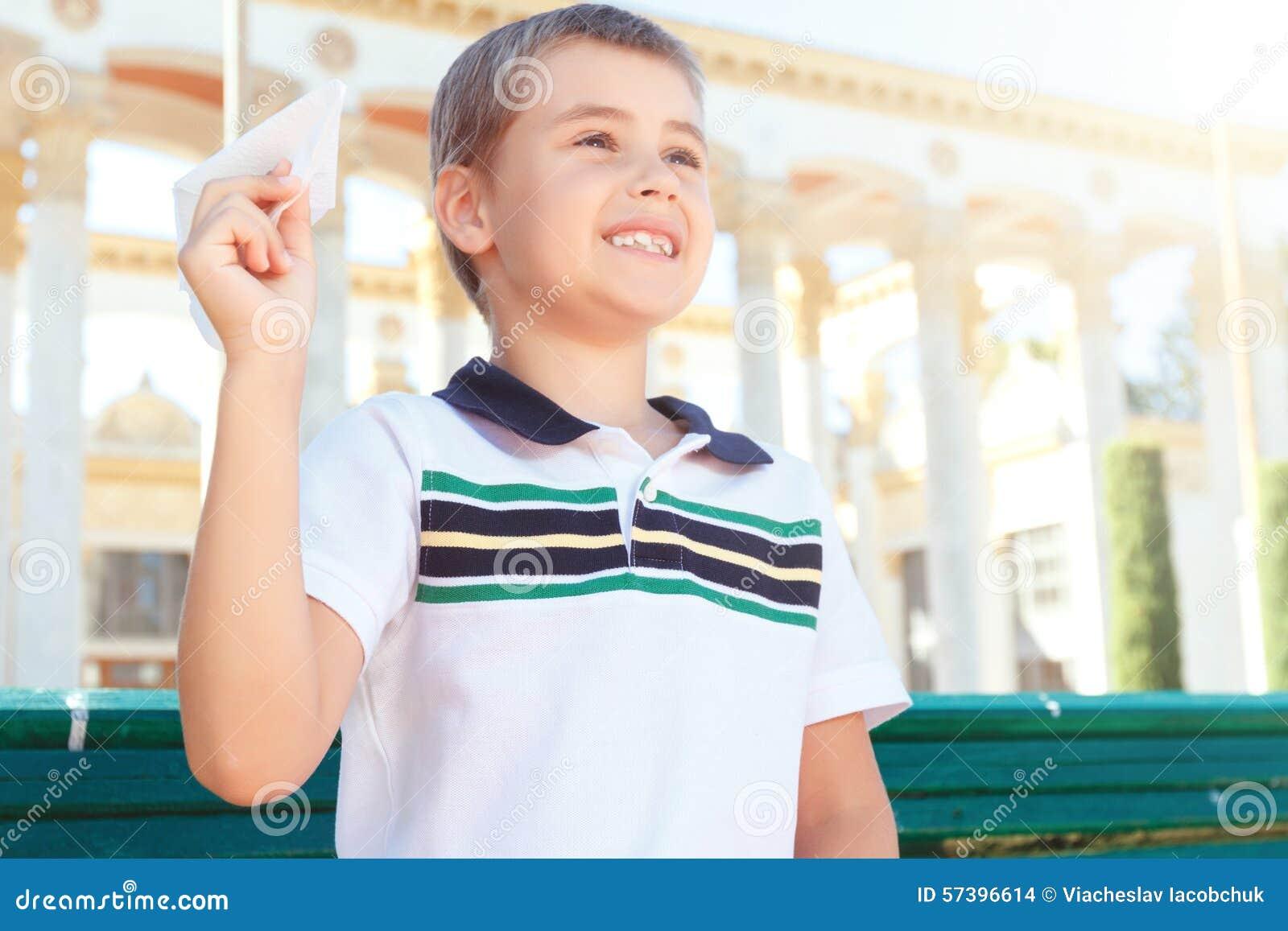 Leuke glimlachende jongen met document vliegtuig