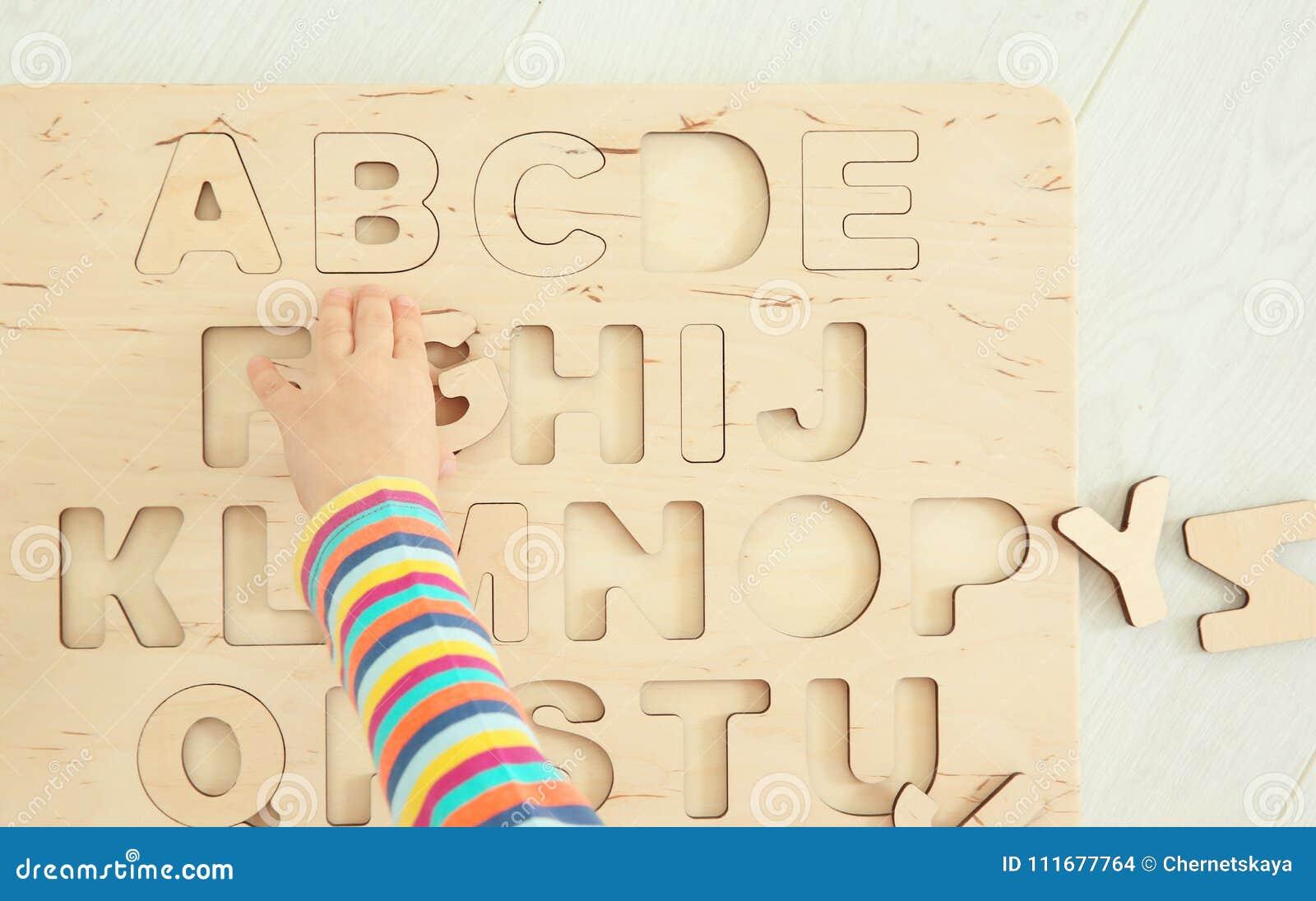 Leuke hand van weinig kind die met brieven spelen