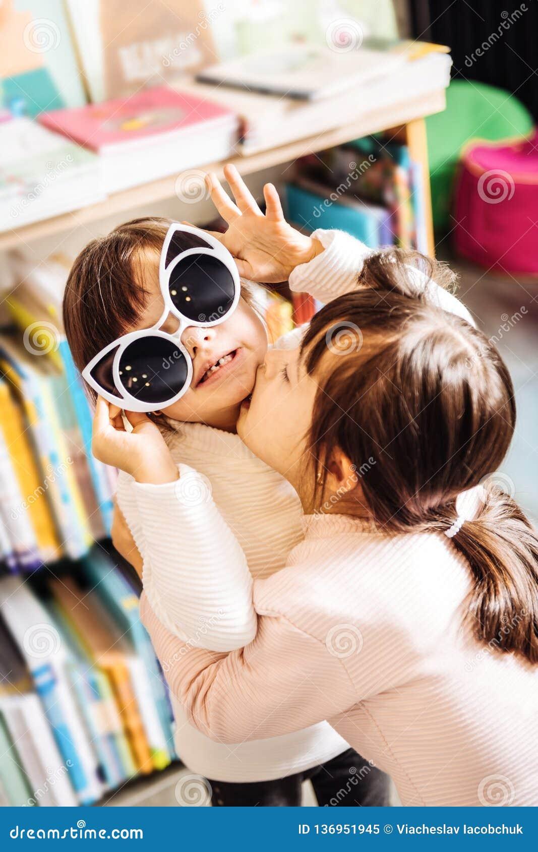 Leuke het houden van donker-haired tweelingen die en elkaar koesteren kussen