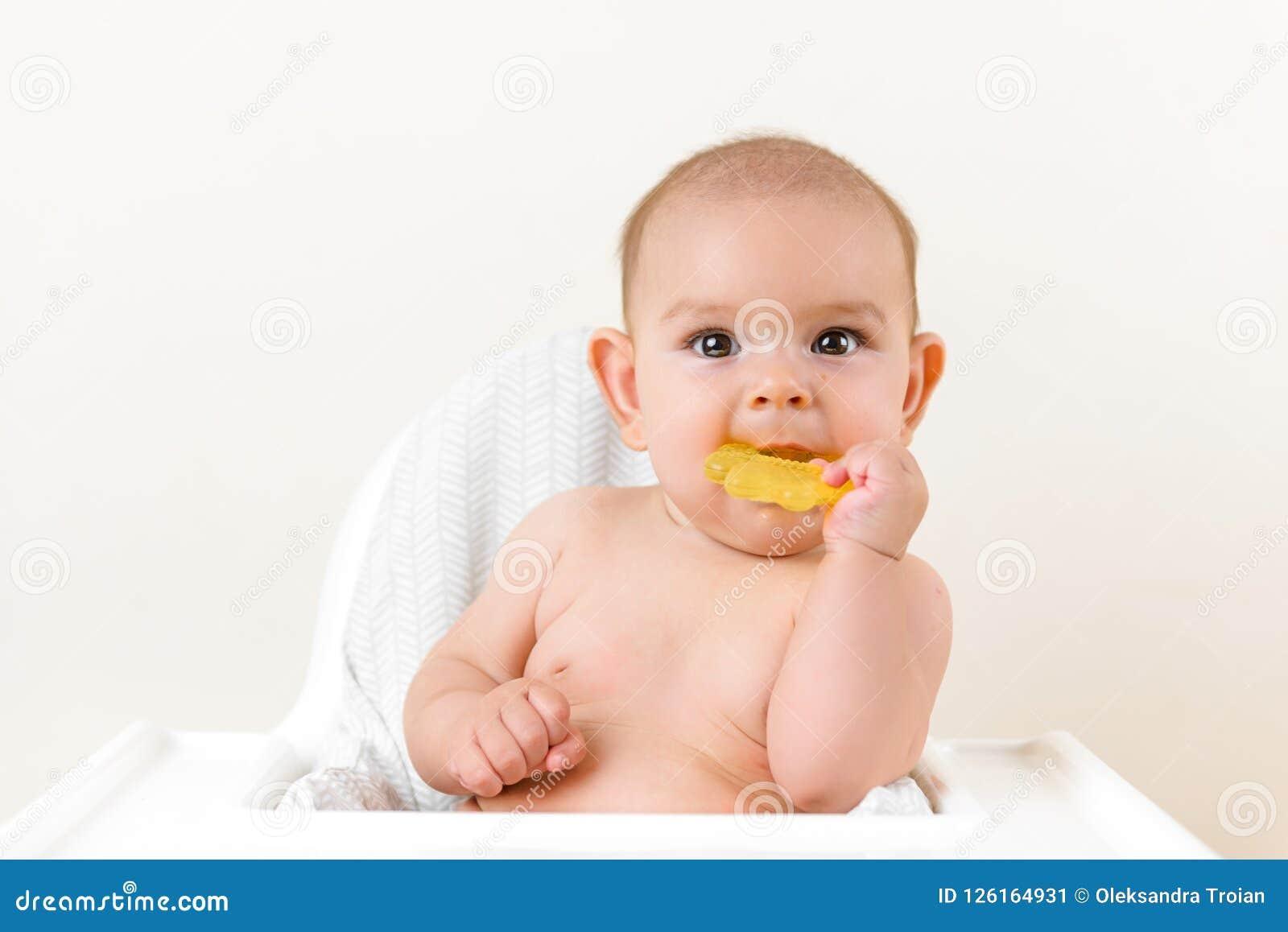 Leuke het jonge geitje van de babyzuigeling het bijten zitting in highchair en het kauwen gele eething stuk speelgoed exemplaar r