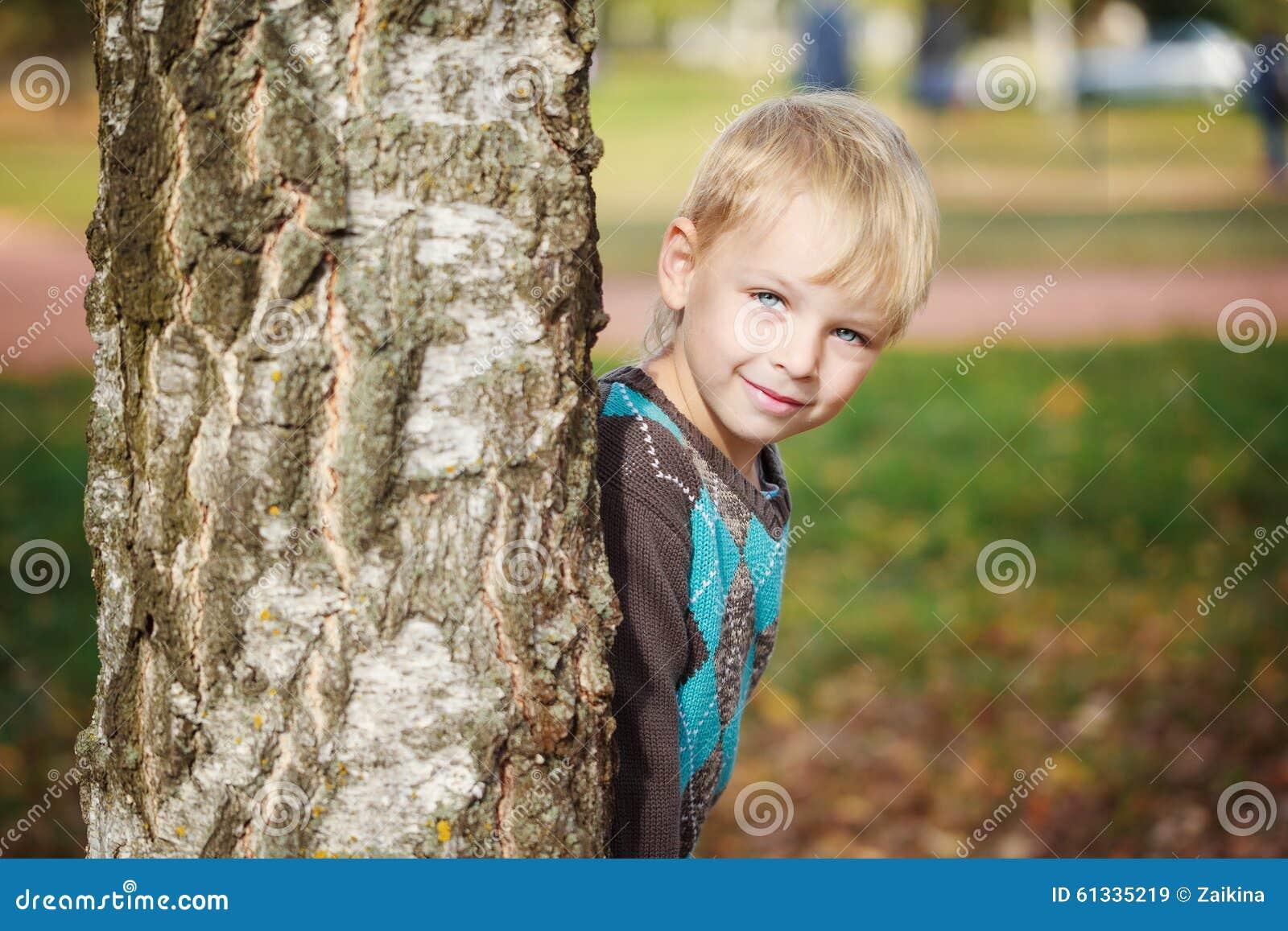 Leuke het portret weinig jongen in een gebreide sweater speelt achter een boom in de herfstpark, huid-en-zoekt het spel bij