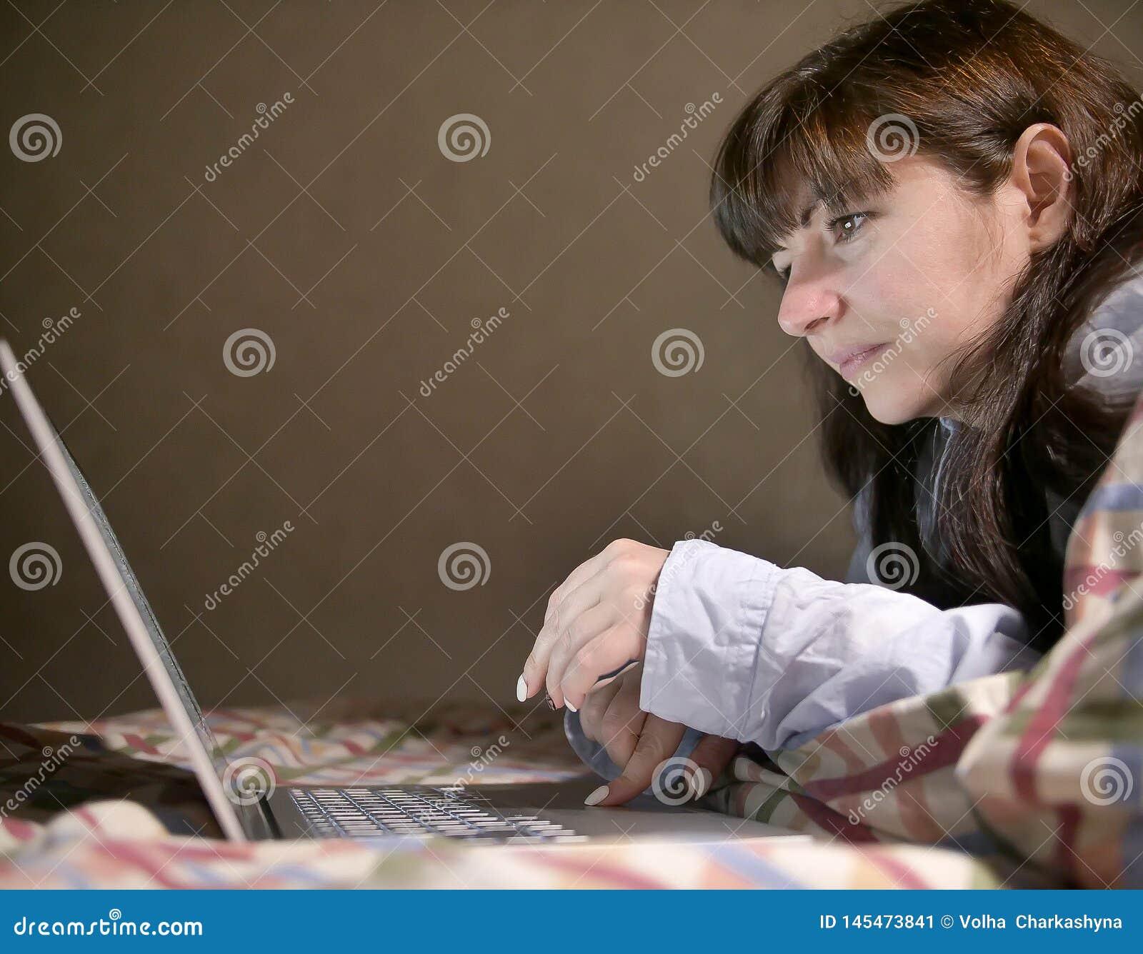 Leuke jonge donkerbruine vrouw die op het bed liggen en in haar laptop typen