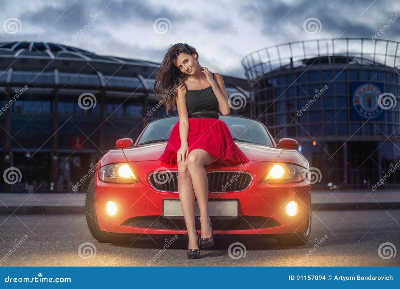 Leuke jonge donkerbruine vrouwenzitting op een bonnet van luxe rode cabriolet auto bij de zonsondergang