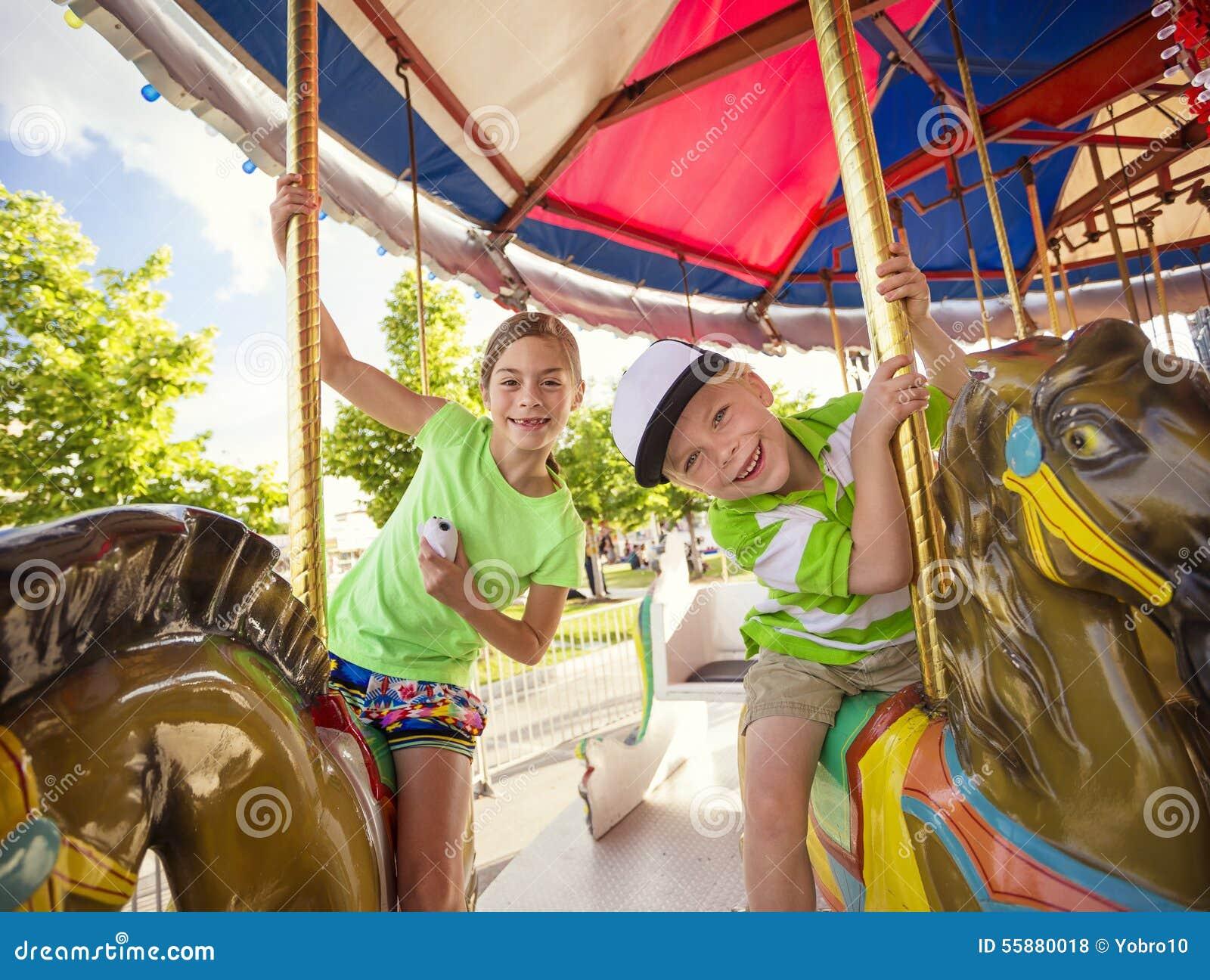 Leuke jonge geitjes die pret hebben die op een kleurrijke Carnaval-carrousel berijden