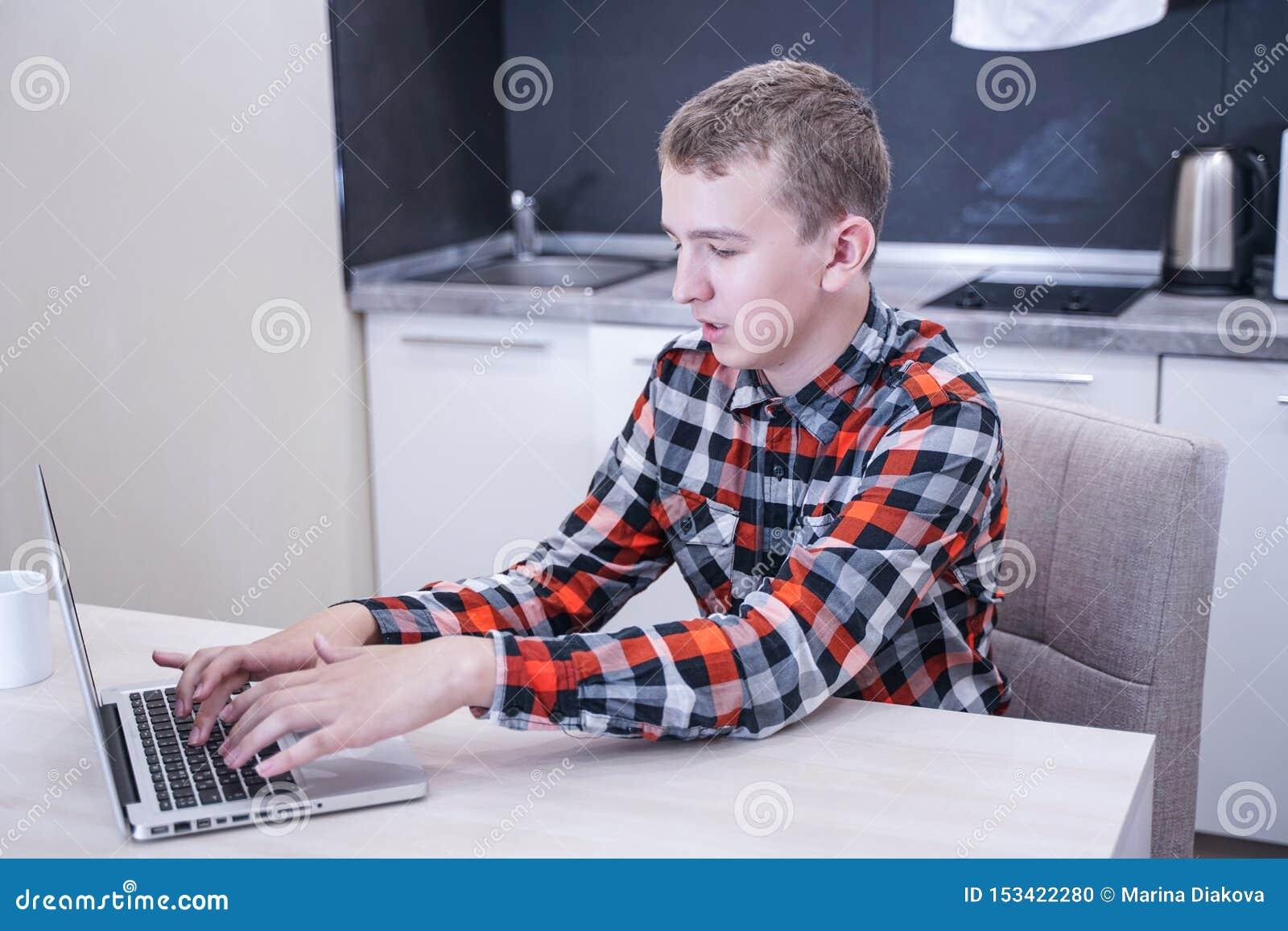 Leuke jonge kerelzitting in een plaidoverhemd met laptop en werken, die thuis alleen bestuderen