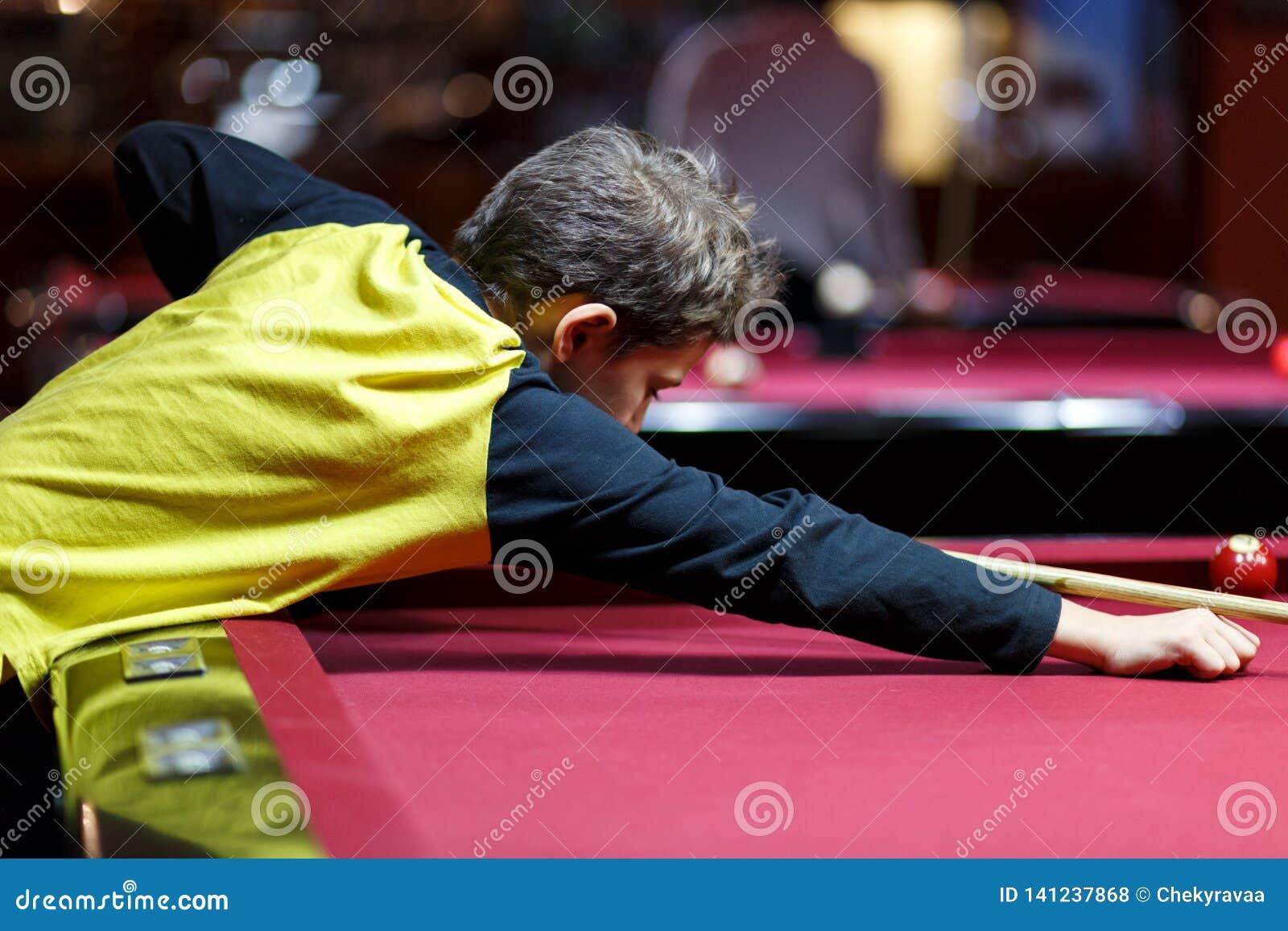 Leuke jongen in het gele biljart van t-shirtspelen of pool in club Het jonge Jonge geitje leert om snooker te spelen Jongen met b