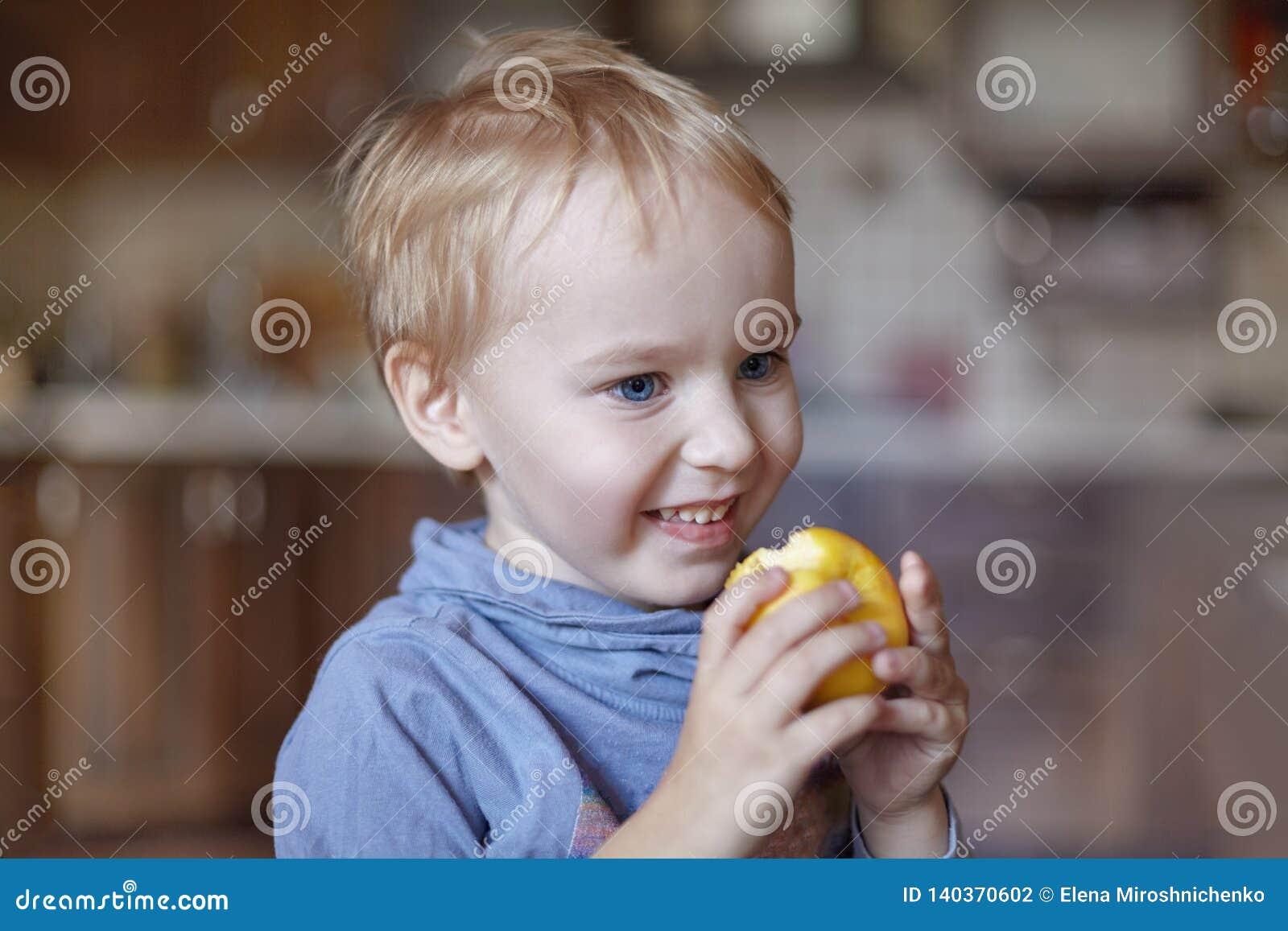 Leuke Kaukasisch weinig jongen met blauw ogen en blondehaar eet gele appel, houdend het op de handen, het glimlachen