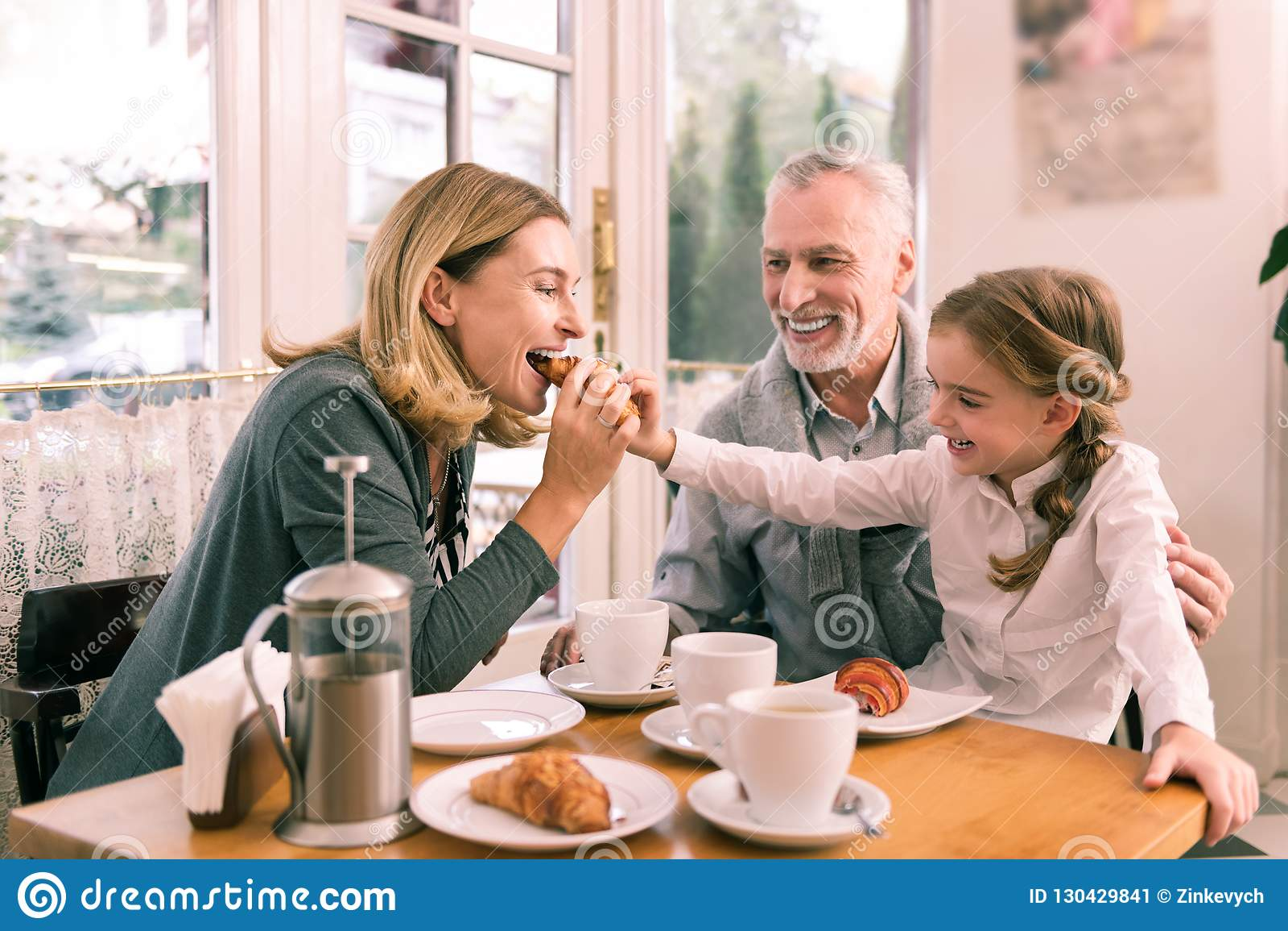 Leuke kind-hearted kleindochter die haar croissant met grootmoeder delen