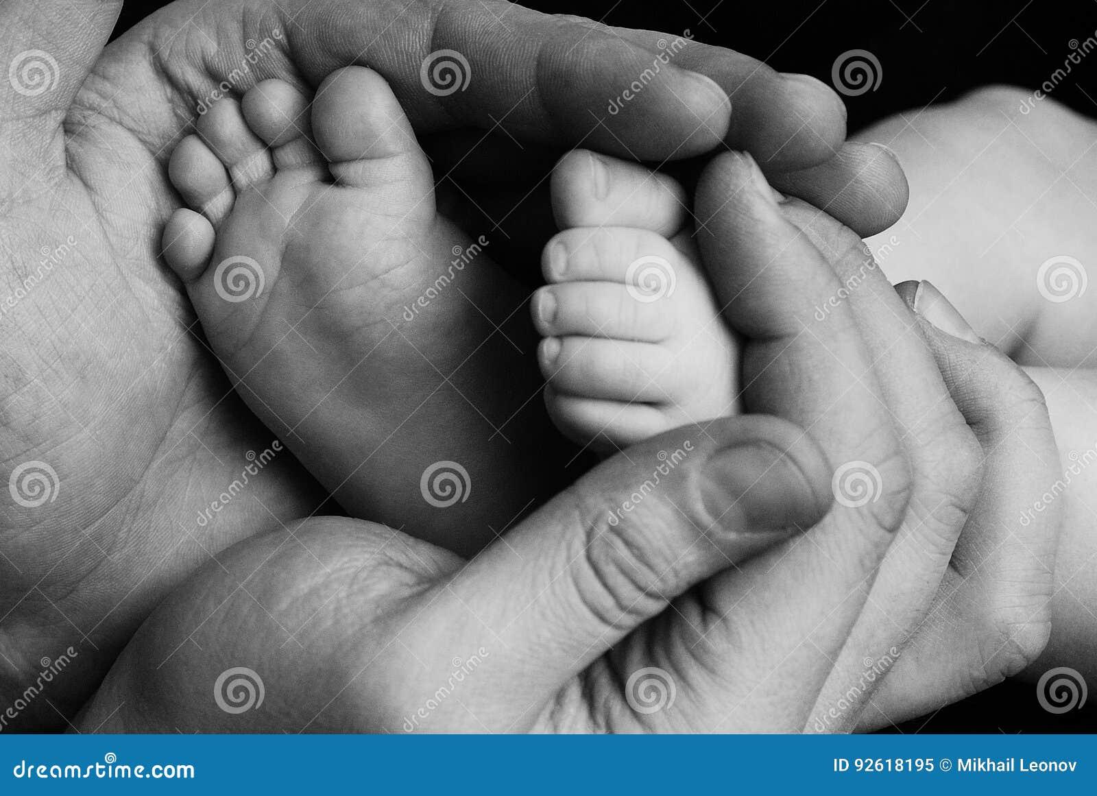 Leuke kindbaby babe weinig voet in de vaderhanden Klassieke die close-up over van familiewaarden en ouders de liefde van kindkind