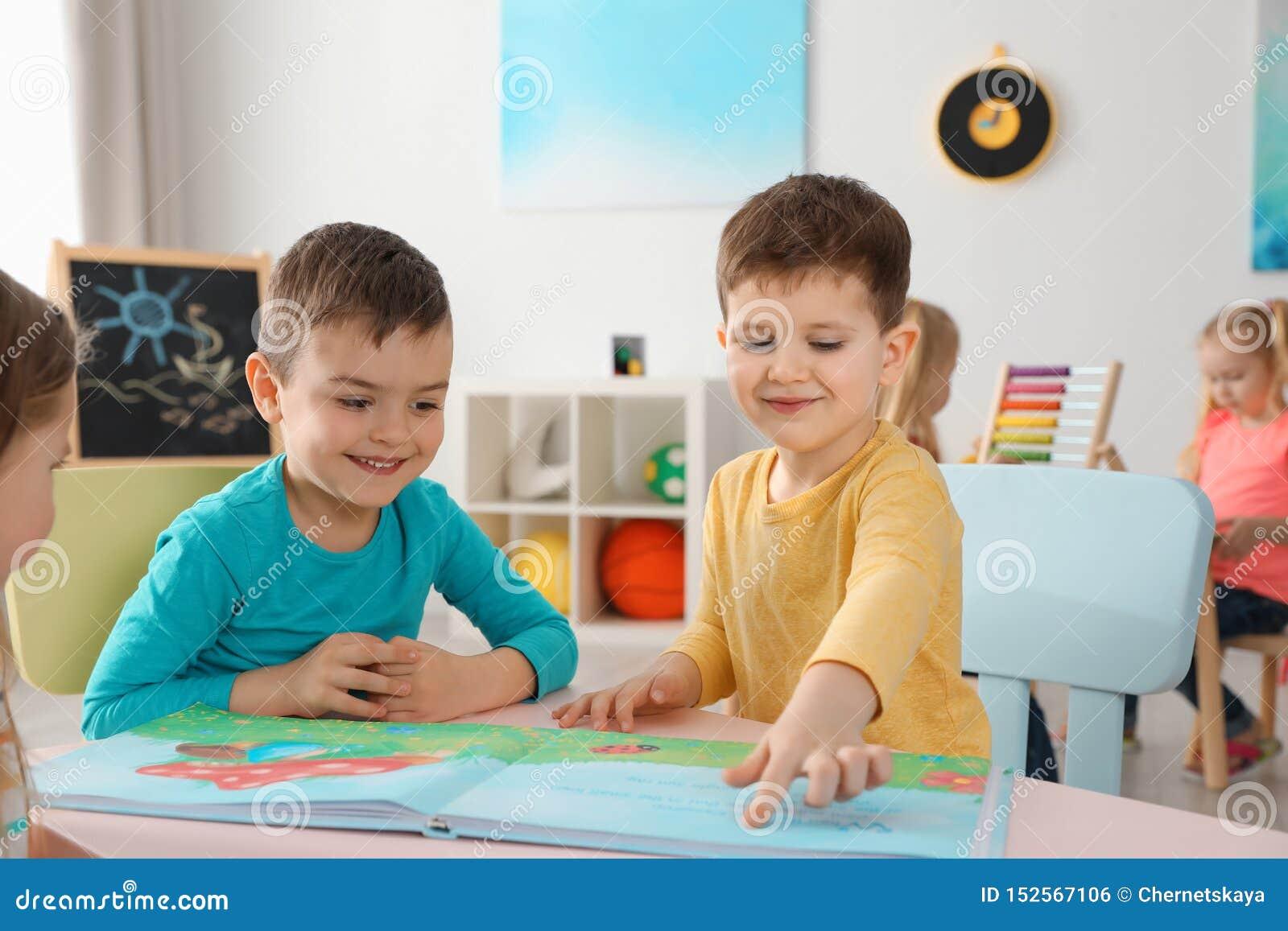 Leuke kleine kinderen die boek lezen samen bij lijst binnen