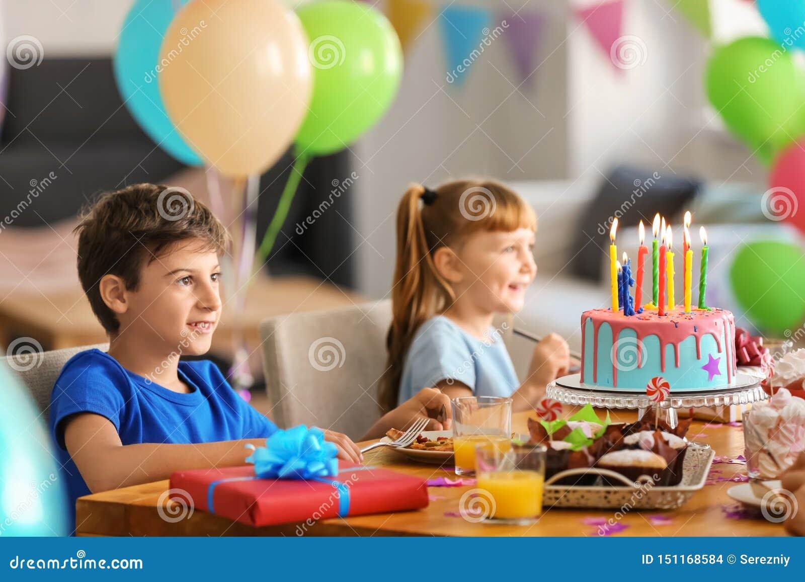 Leuke kleine kinderen die smakelijke pizza en snoepjes eten bij verjaardagspartij