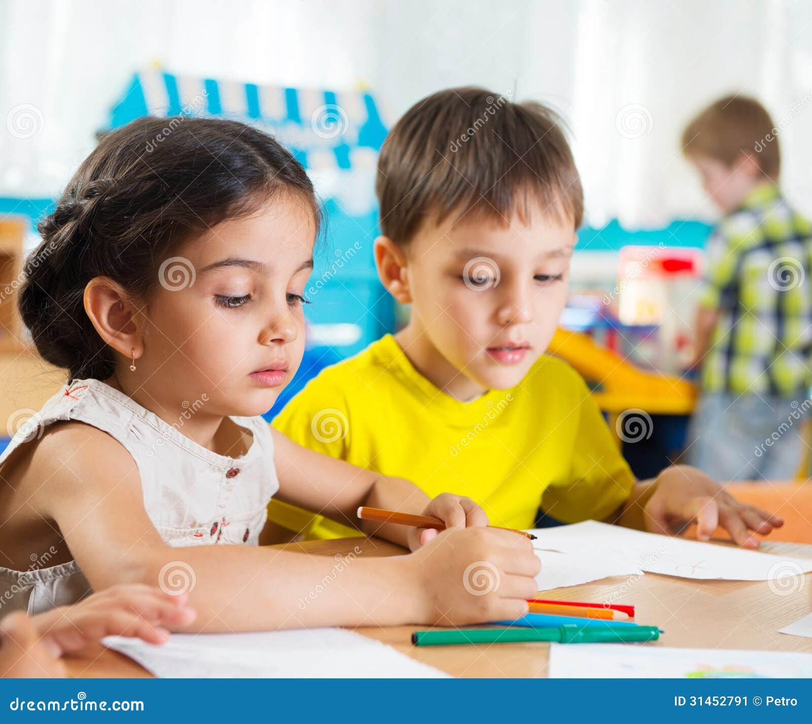 Leuke kleuters die met kleurrijke potloden trekken