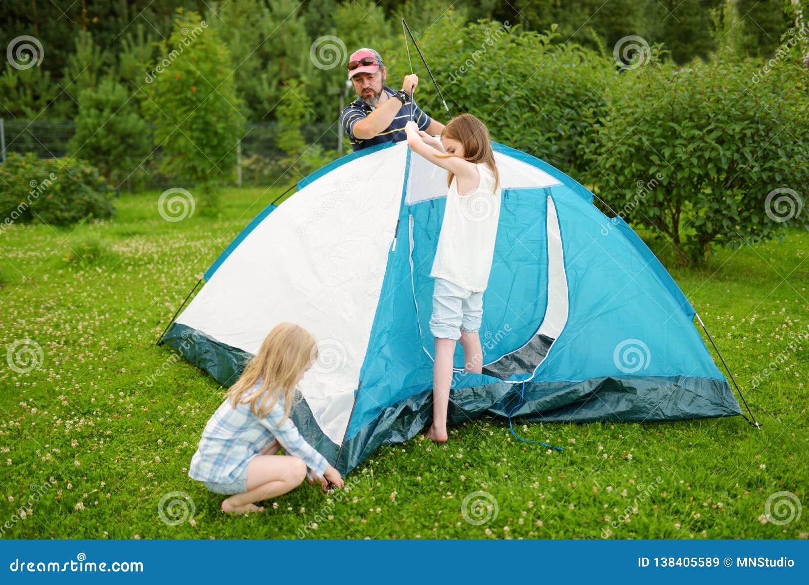 Leuke meisjes die hun ouder helpen aan opstelling een tent op een kampeerterrein Actieve levensstijl, familie recreatief weekend