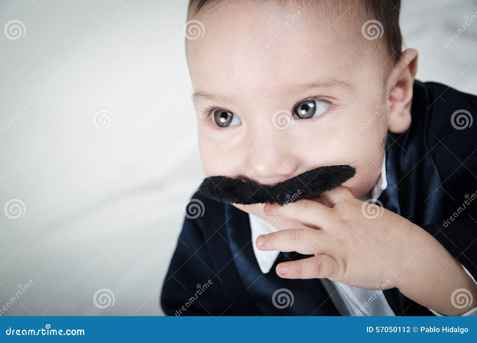 Leuke mooie babyjongen in kostuum met snor