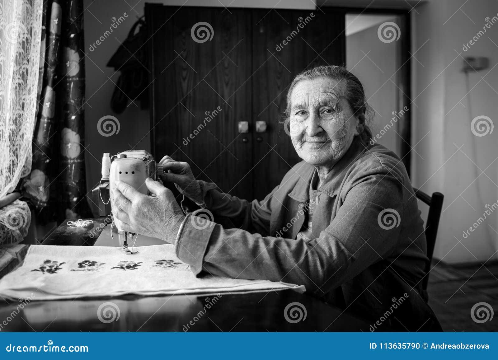 Leuke 80 plus éénjarigen hogere vrouw die uitstekende naaimachine met behulp van Zwart-wit beeld van aanbiddelijke bejaarde naaie