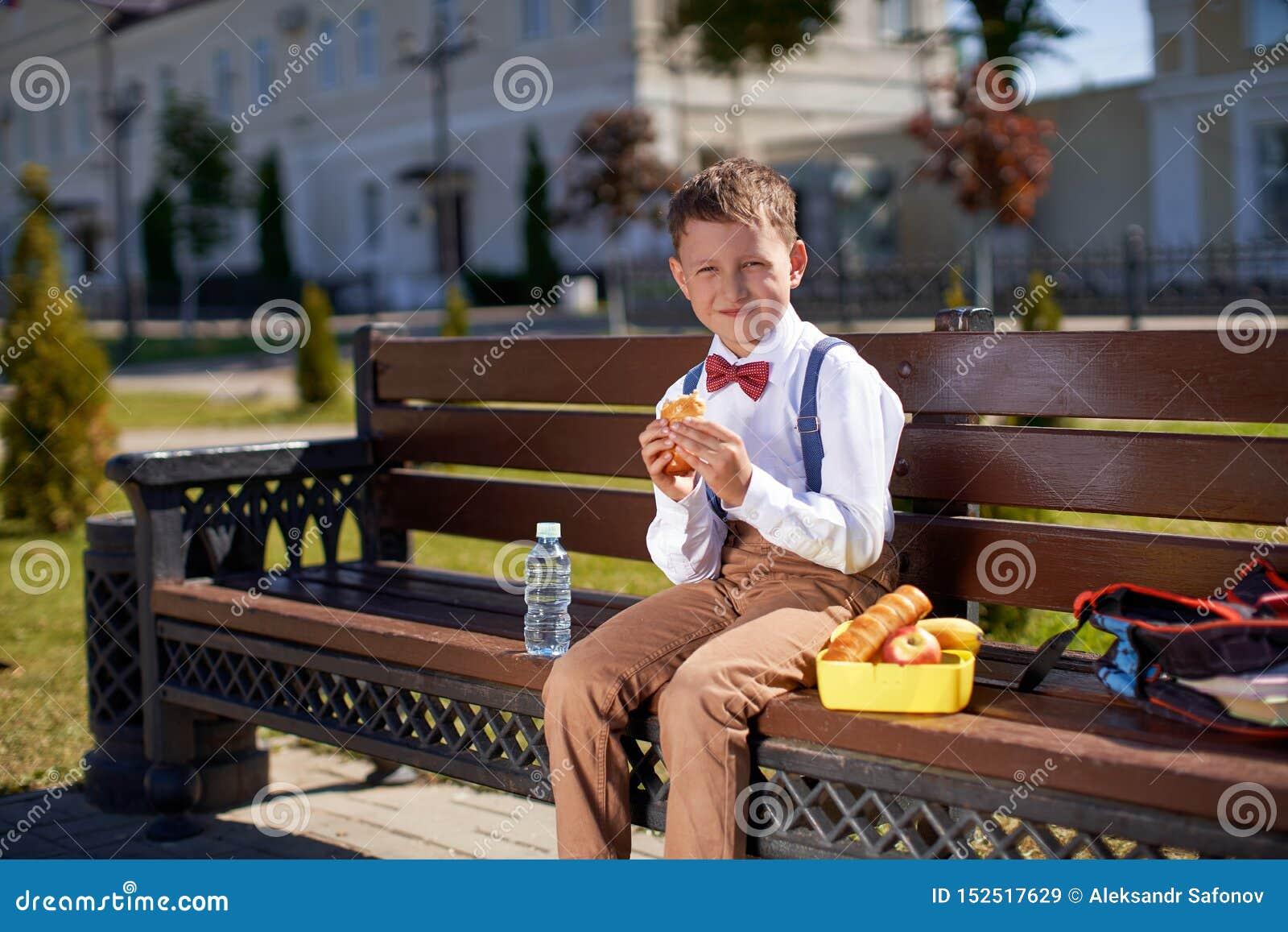 Leuke schooljongen die in openlucht de school eten Gezond schoolontbijt voor kind Voedsel voor lunch, lunchboxes met sandwiches,