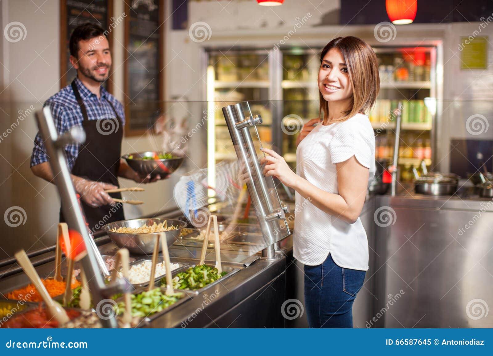Leuke Spaanse vrouw bij een saladebar