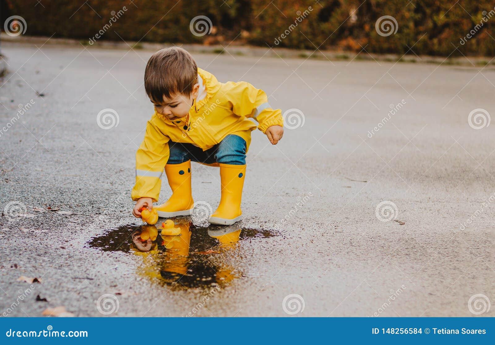 Leuke speels weinig babyjongen in heldere gele regenjas en rubberlaarzen die met rubbereenden in kleine vulklei bij de regenachti