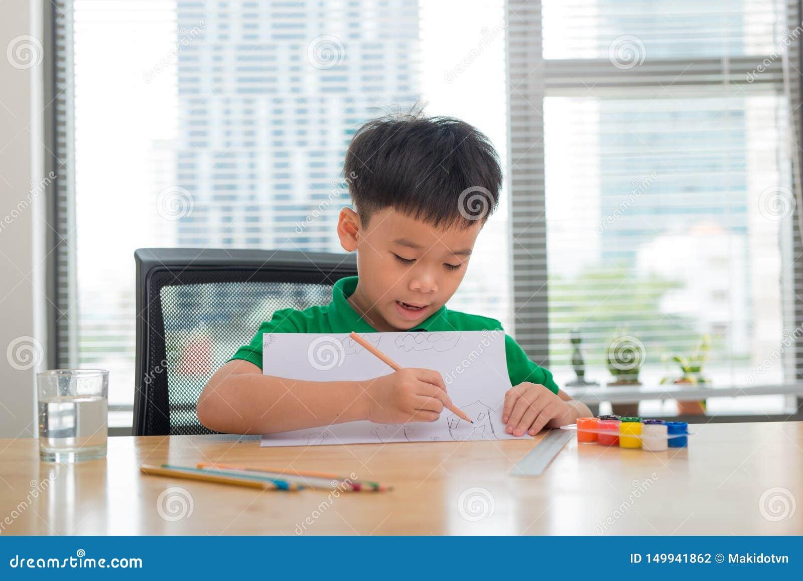 Leuke verwarde glimlachende jongen die thuiswerk, het kleuren van pagina s, het schrijven en het schilderen doen De kinderen schi