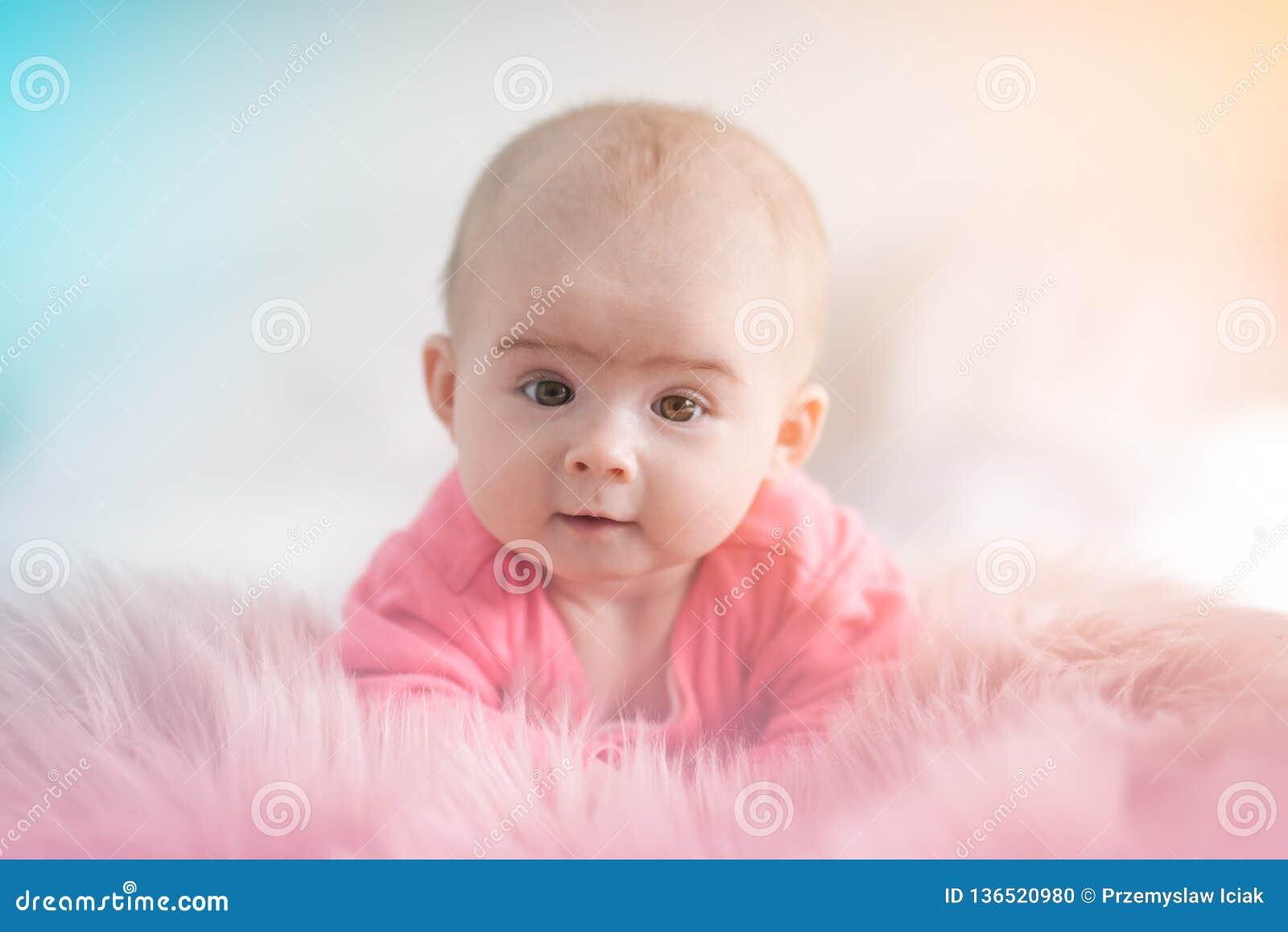 Leuke vijf maanden oud van het Babymeisje de zuigelings op een bed op haar buik met hoofd die omhoog naar camera met haar grote o