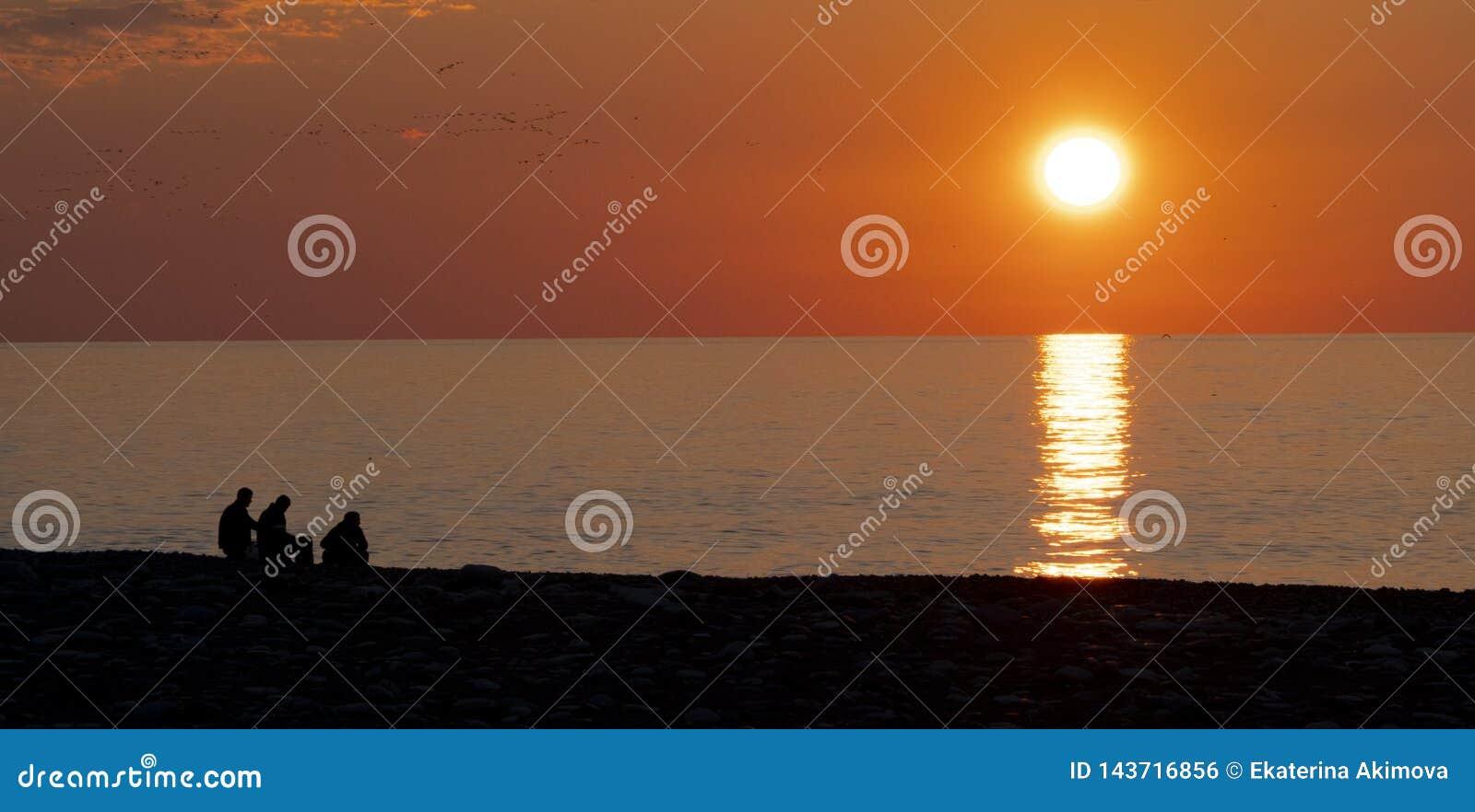 Leute auf dem Hintergrund des Sonnenuntergangs und das Meer auf der Ufergegend