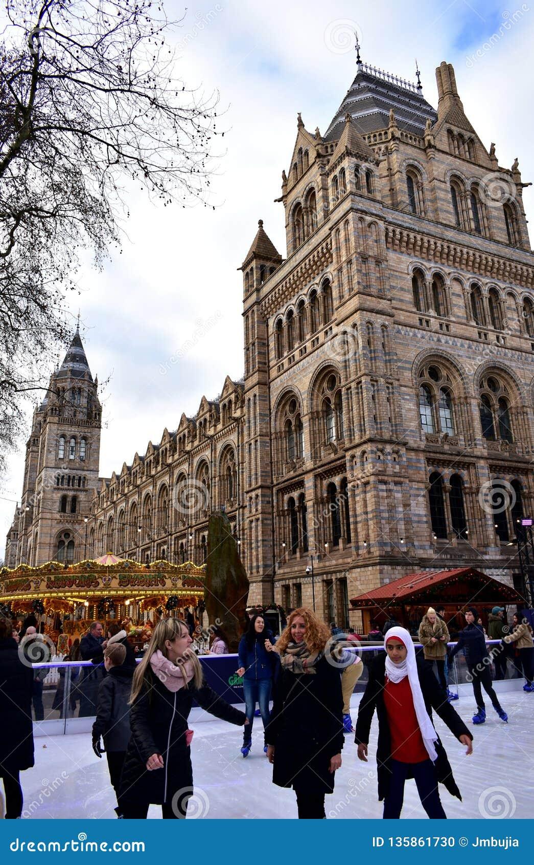 Leute, die auf Eis an der Naturgeschichtliches Museums-Weihnachtseisbahn eislaufen London, Vereinigtes Königreich, im Januar 2019