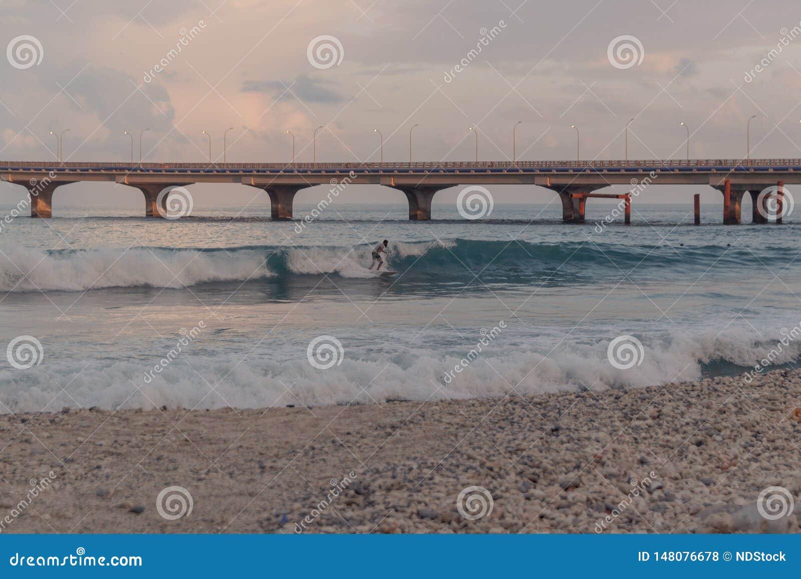 Leute, die in einen kleinen Strand im Mann, Malediven surfen