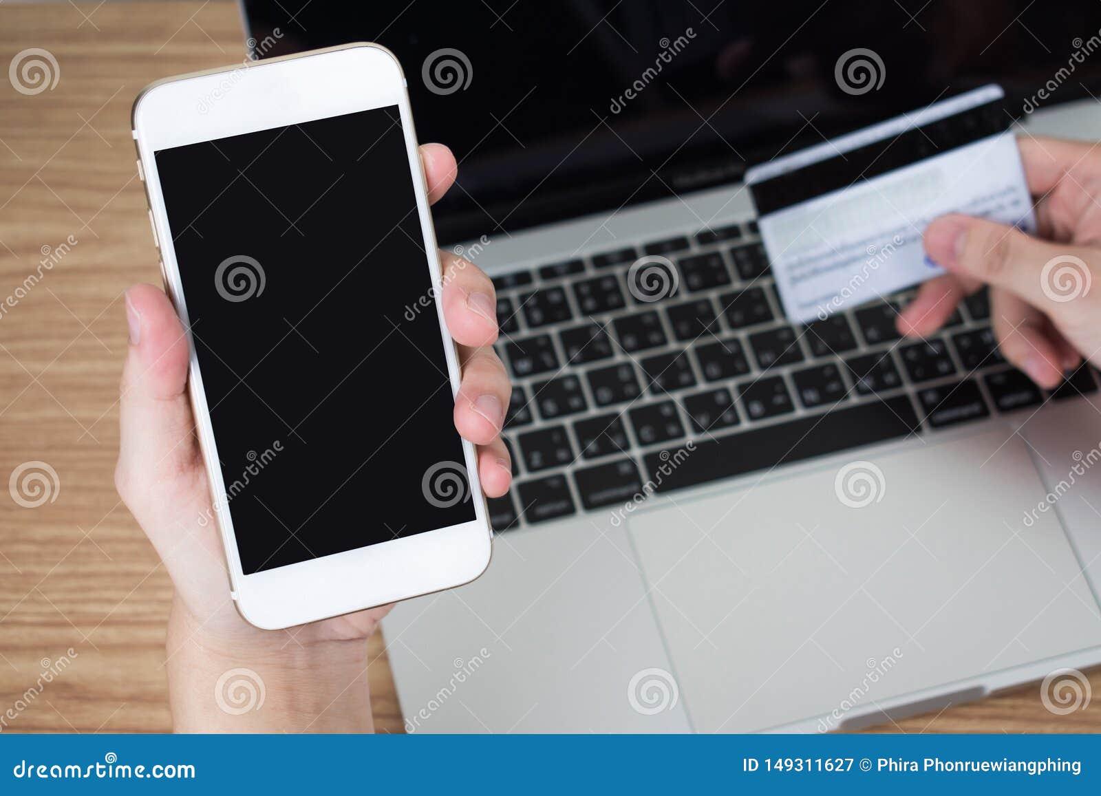 Leute, die im Raum unter Verwendung eines Smartphone, zahlend ?ber eine Kreditkarte auf einem Holztisch sitzen Schwarzer Bildschi