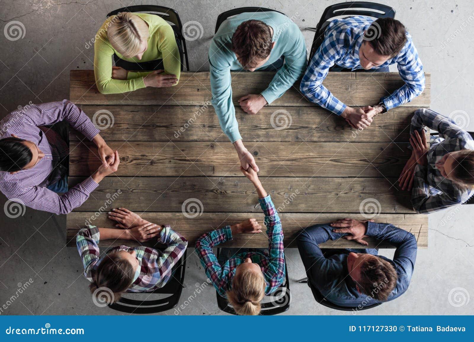 Leute, die um die Tabelle gibt Hoch fünf sitzen