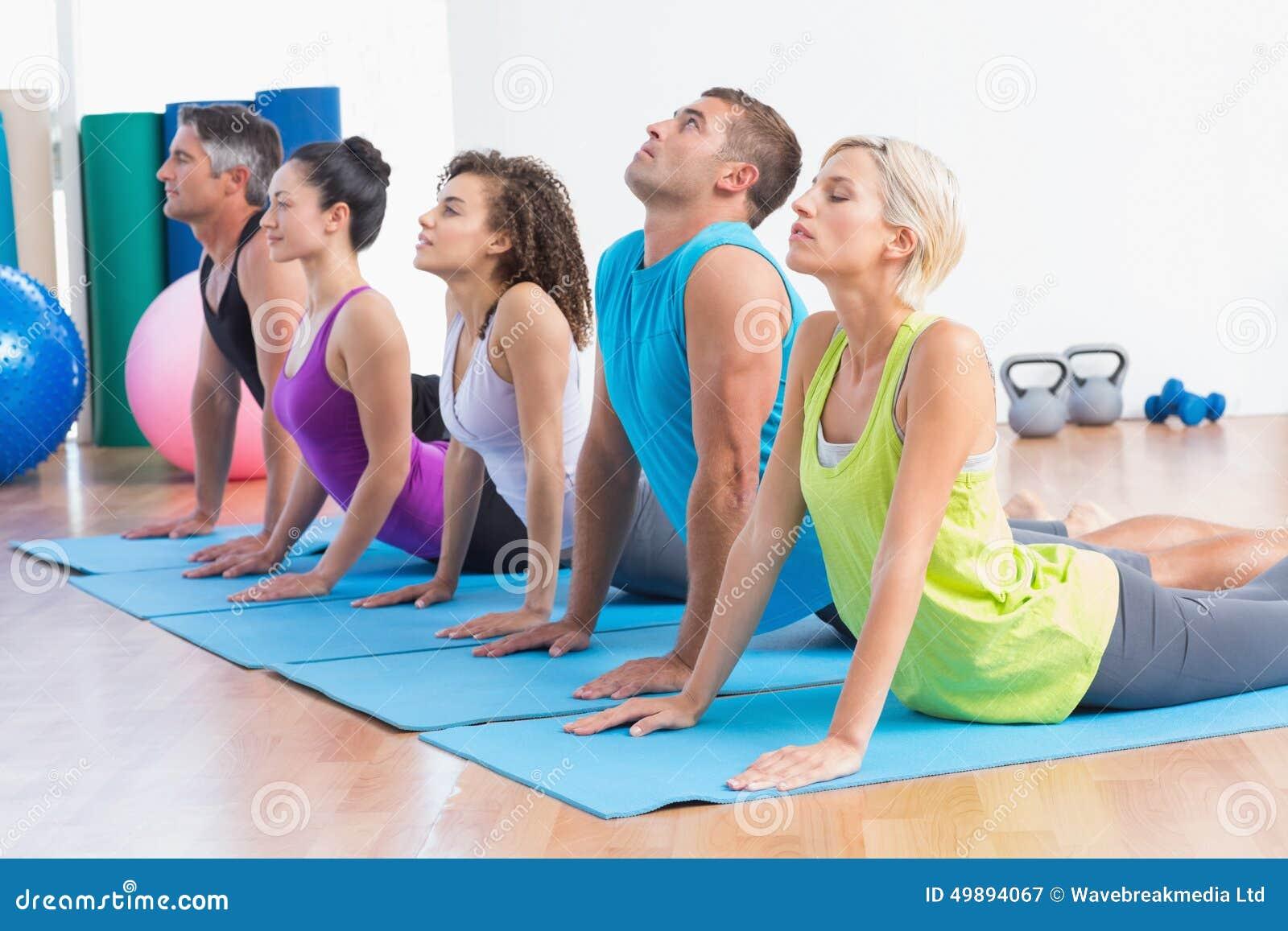 Leute, die Yogaausdehnung im Sportunterricht tun