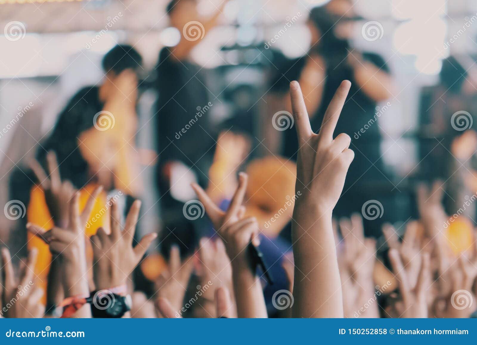 Leute hielten zwei Finger am Konzert
