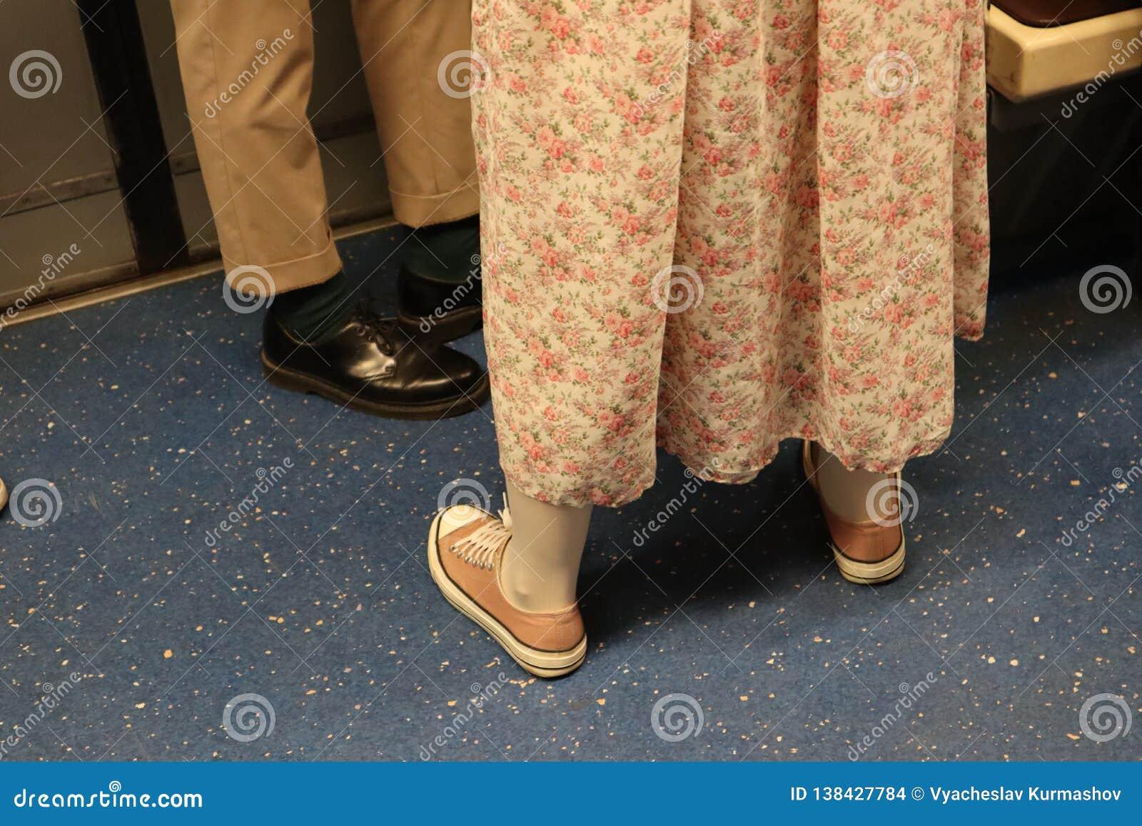 Leute stehen im Zug betrachten Sie ihre Schuhe Mädchen in einem langen rosa Kleid und in rosa Turnschuhen