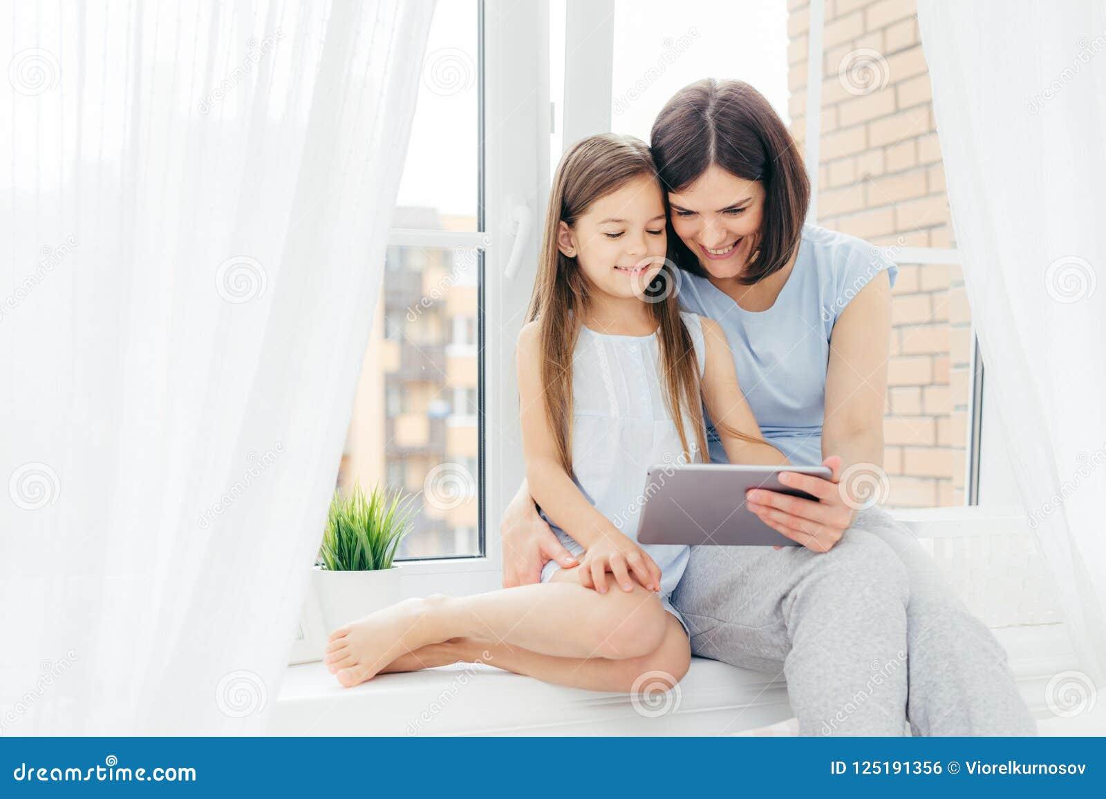 Leute, Technologie, Familie, Kinderkonzept Positive junge andere und ihre kleine Tochter auf Fensterbrett, digitale Tablette des