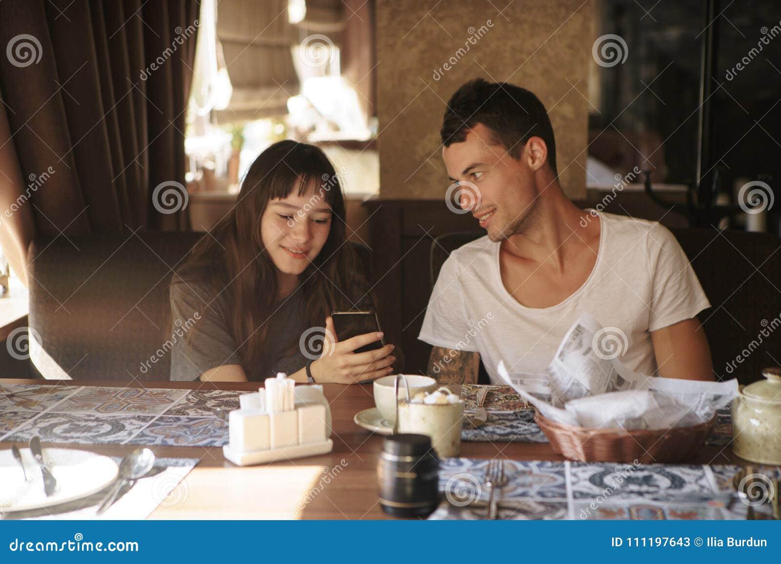 Leute, Technologie, Lebensstil und Datierungskonzept - glückliches Paar mit Smartphone trinkendem Kaffee und Smoothie am Café