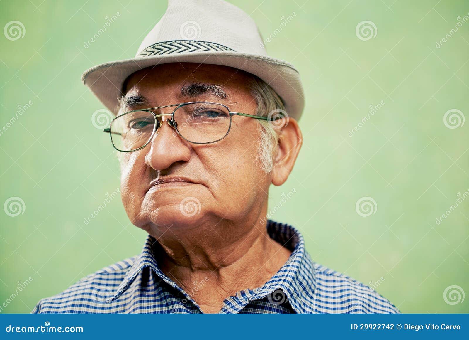 Porträt des ernsten alten Mannes mit dem Hut, der Kamera betrachtet