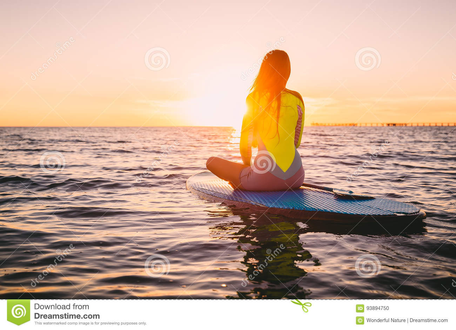 Levántese el embarque de la paleta en un mar reservado con colores calientes de la puesta del sol del verano Relajación en el océ