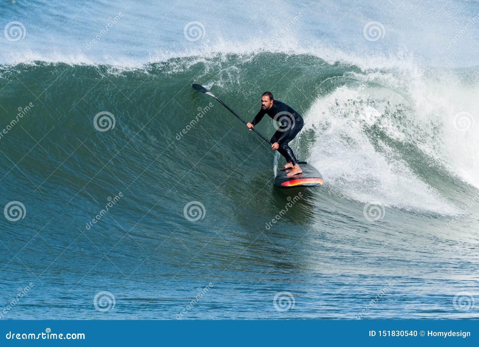 Lev?ntese a la persona que practica surf de la paleta