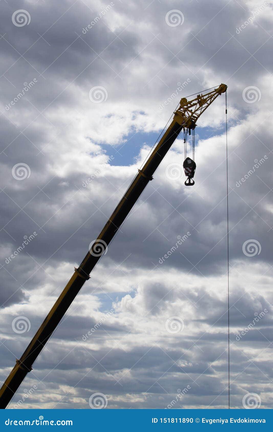 Levage de la grue à un chantier de construction contre un ciel nuageux