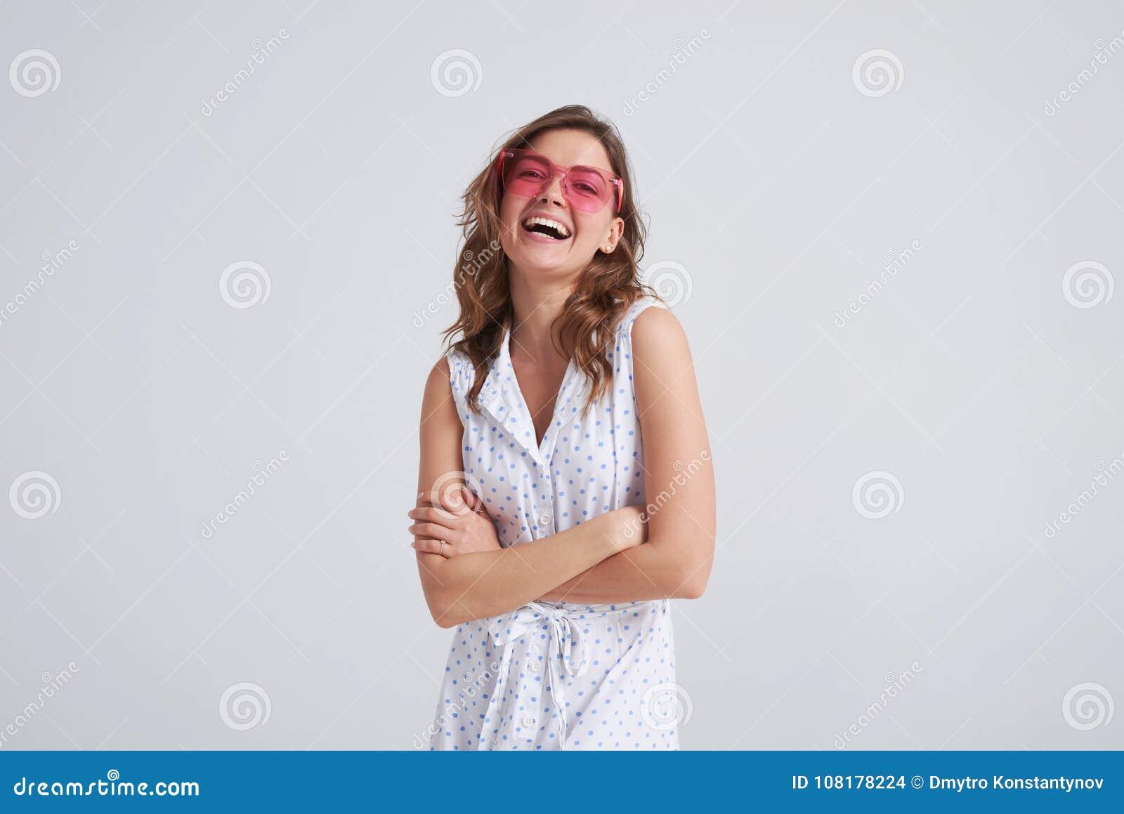 Levantamento bonito de riso do vestido e dos óculos de sol da menina