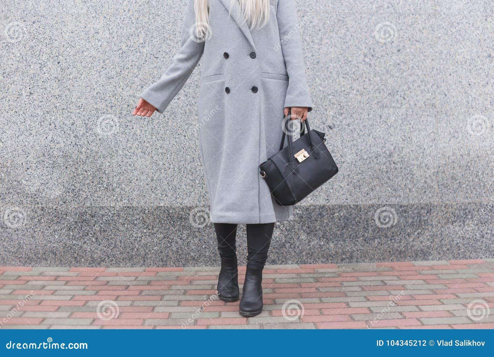 Levantamento da mulher elegante exterior, guardando o saco de couro preto, botas à moda vestindo, revestimento elegante Conceito