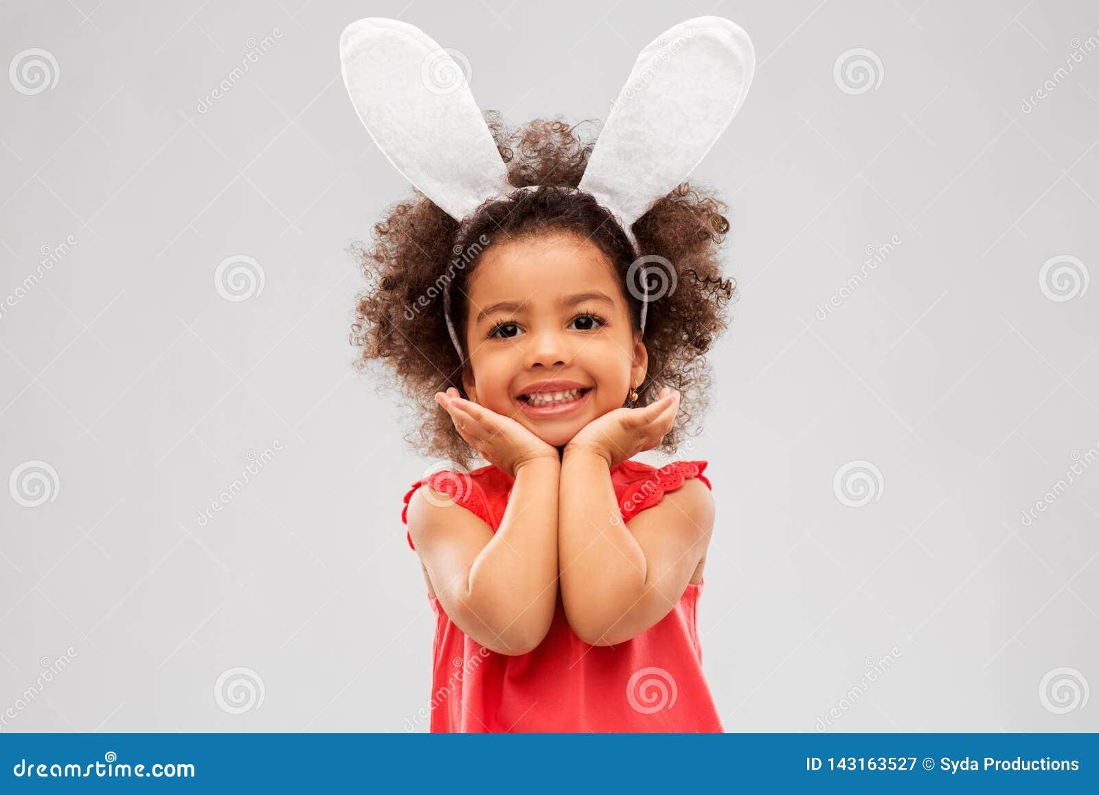 Levantamento vestindo das orelhas do coelhinho da Páscoa da menina feliz