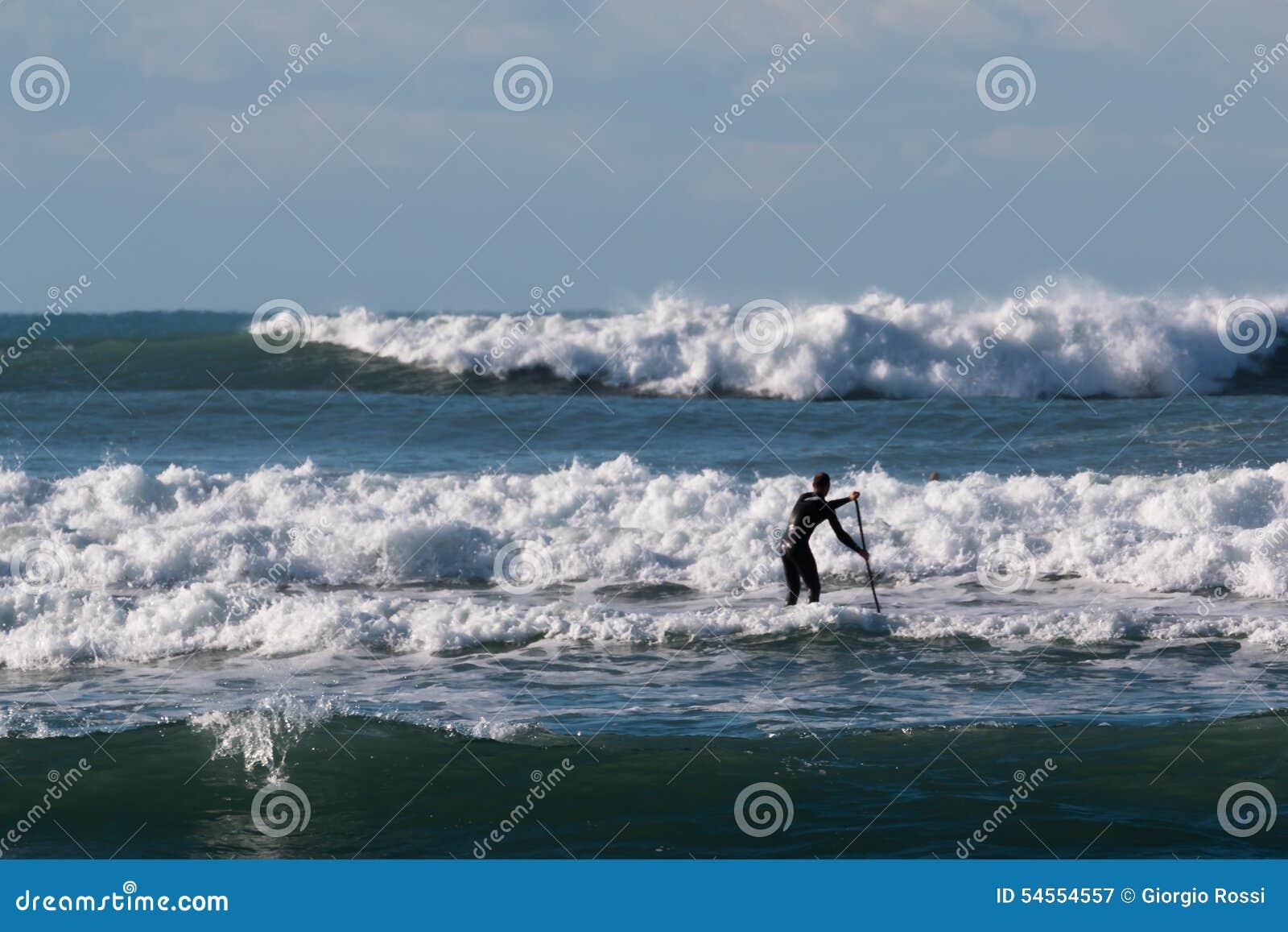 Levante-se a placa de pá, homem do surfista que paddleboarding a bordo