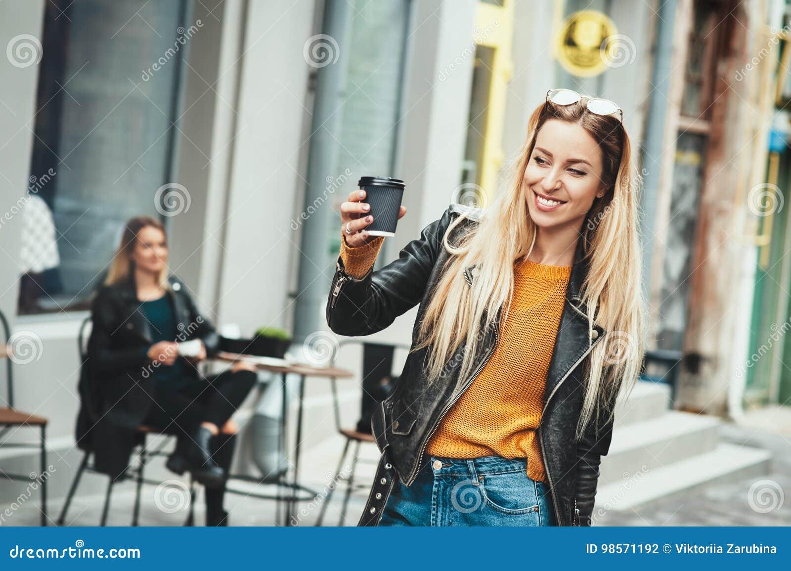 Leve embora o café Mulher urbana nova bonita que veste na roupa à moda preta que guarda o copo de café e que sorri ao andar avant